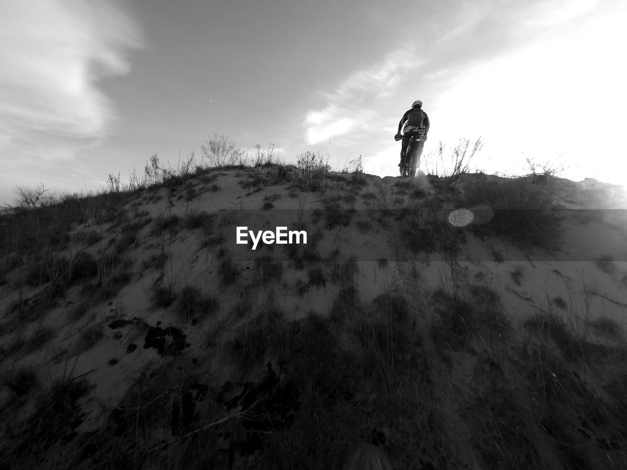 LOW ANGLE VIEW OF PERSON ON MOUNTAIN AGAINST SKY