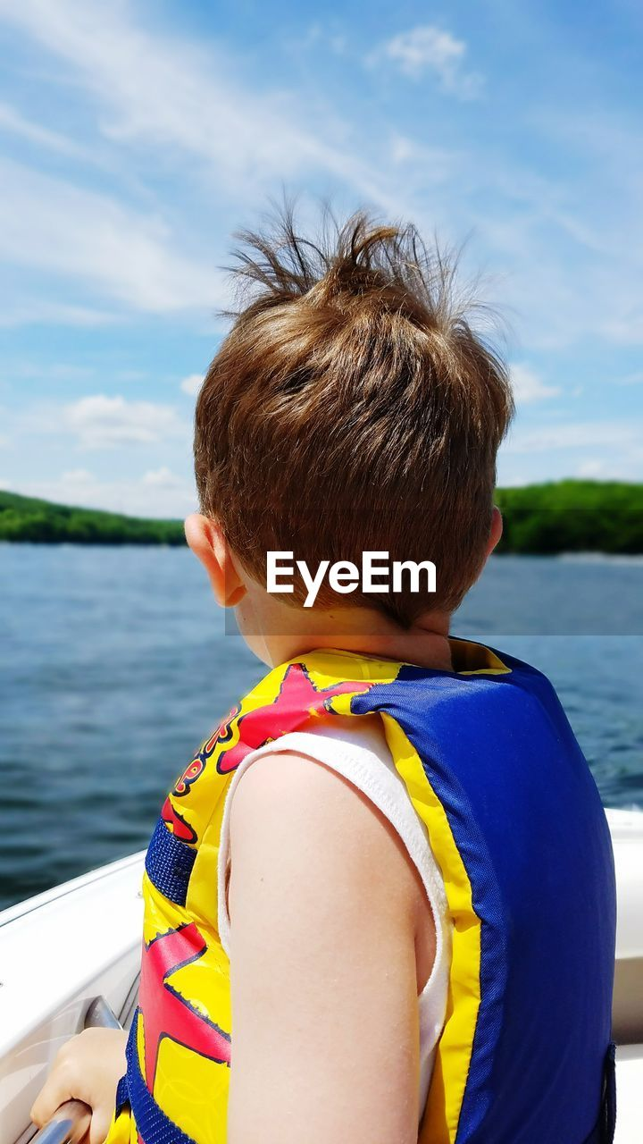 Boy Wearing Life Jacket Sitting In Boat On River Against Sky