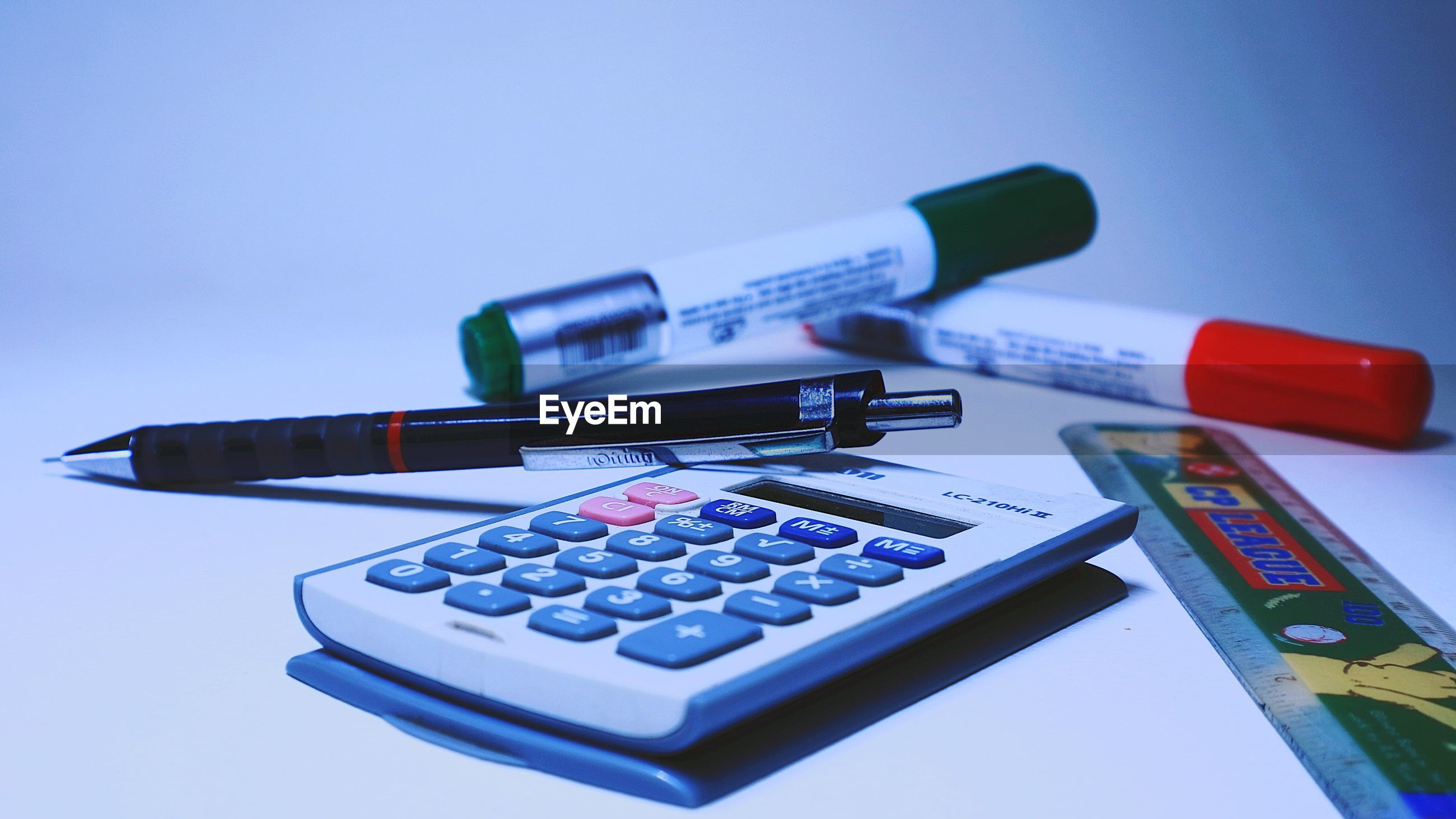 Close-up of calculator and writing instrument on table