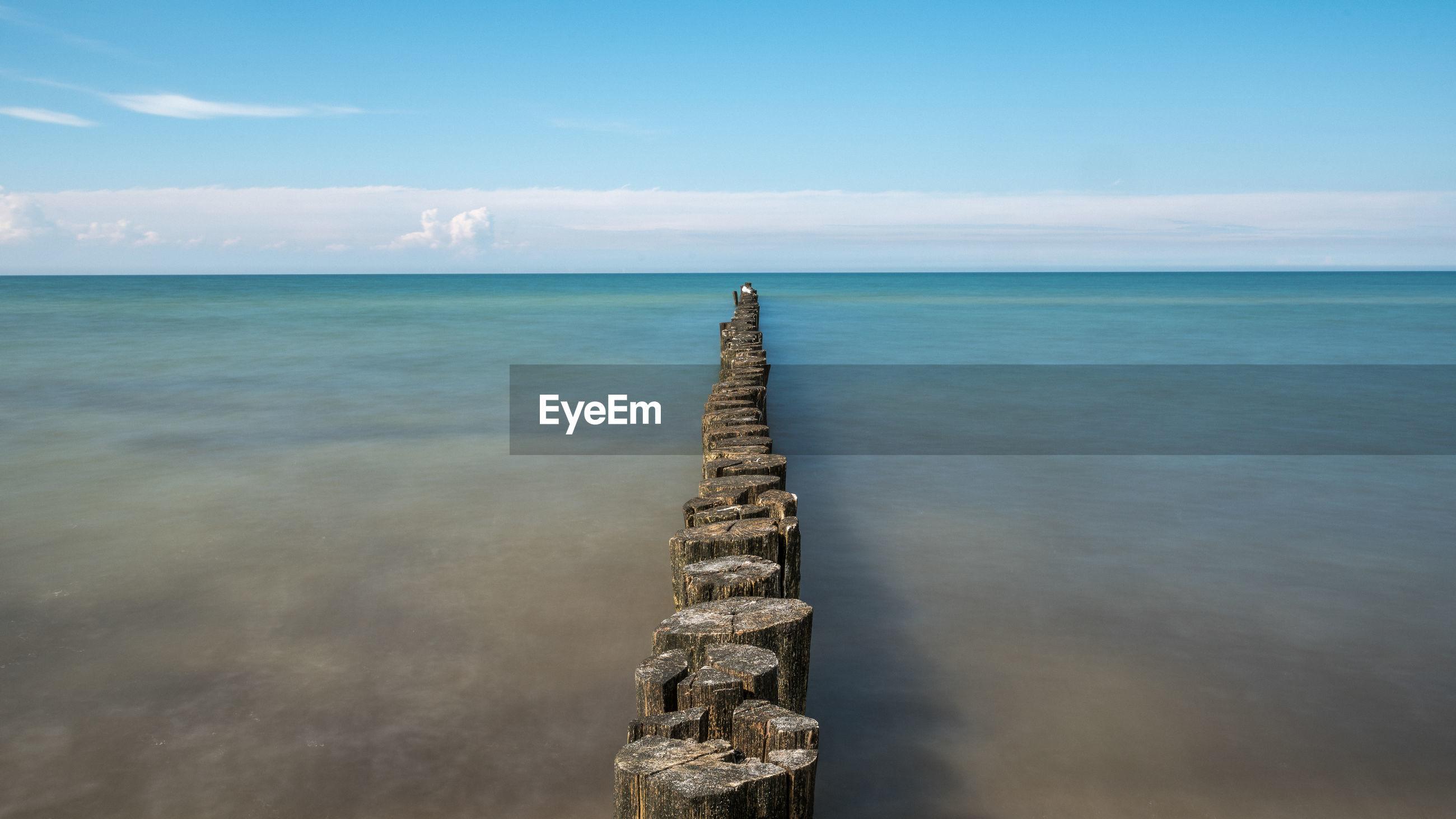 Wooden stumps in calm blue sea