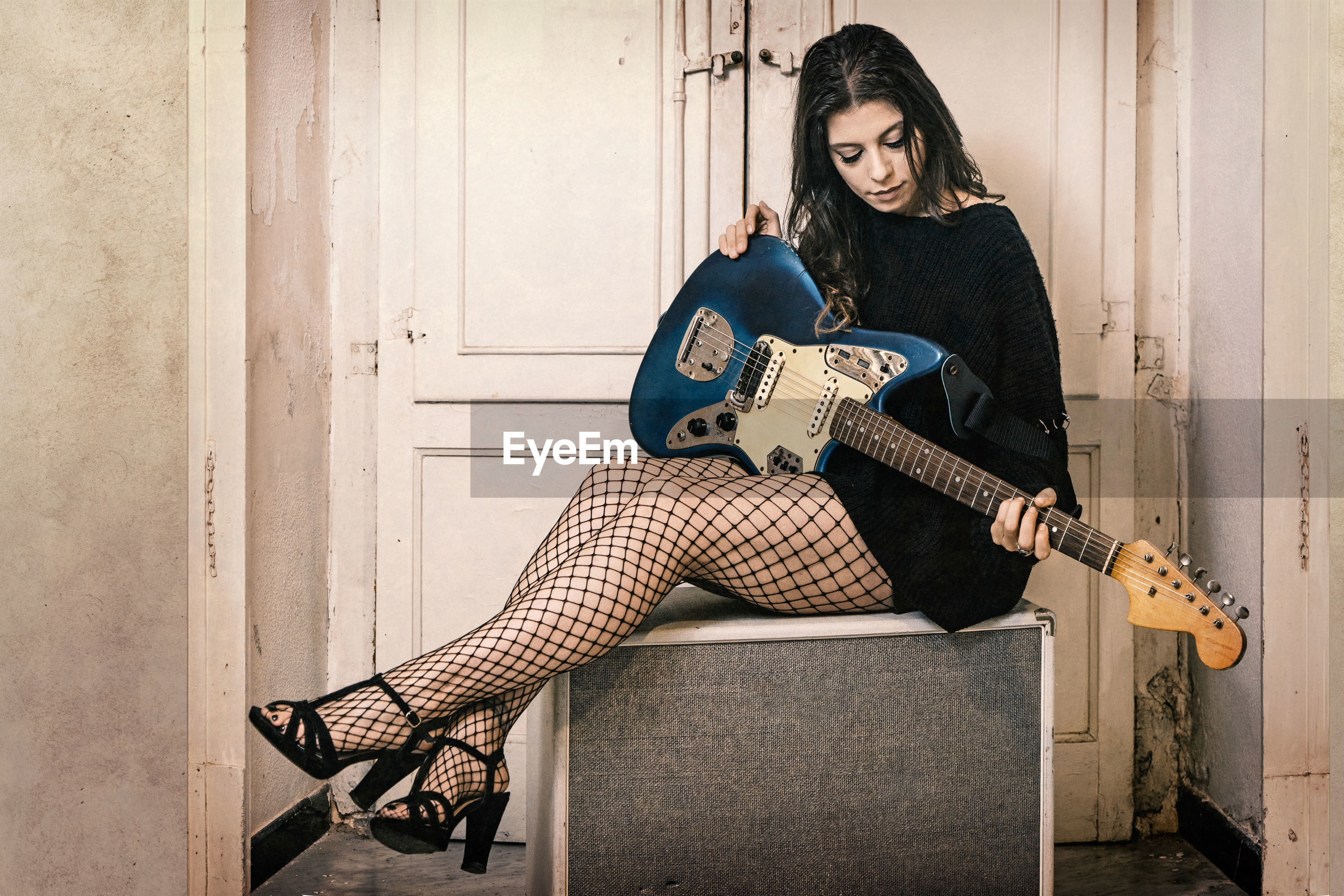Full length of young woman playing guitar while sitting against doors