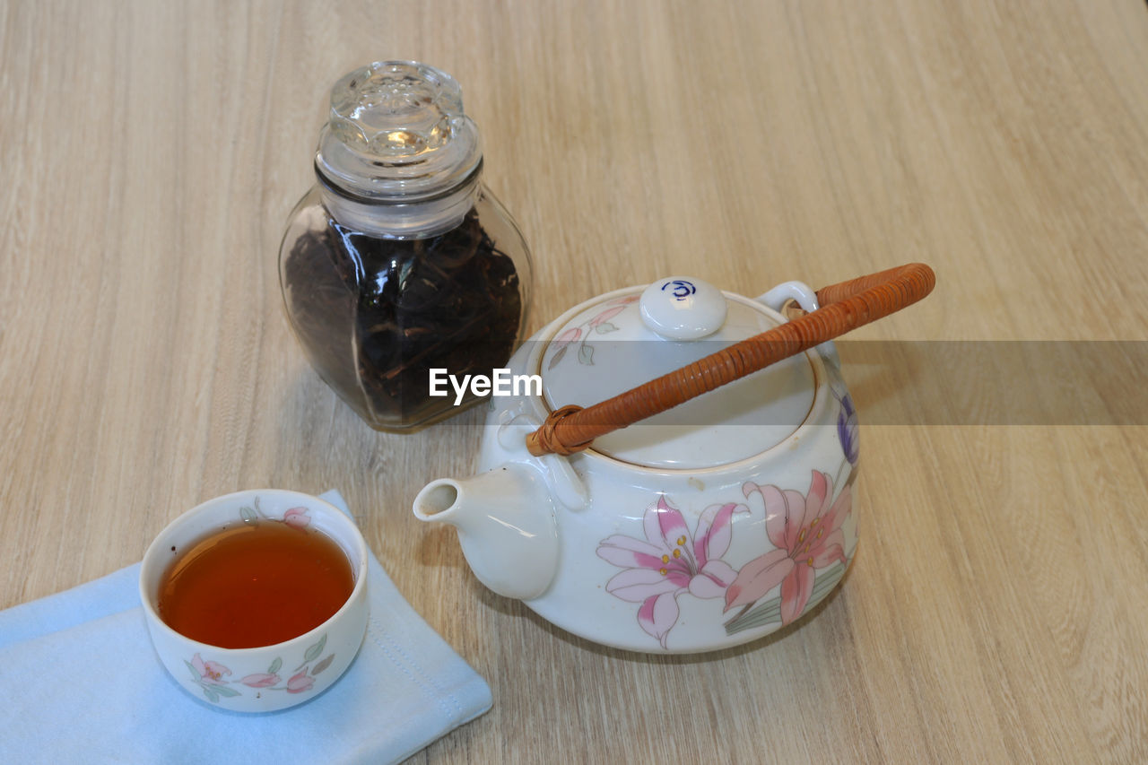 food and drink, table, drink, food, cup, refreshment, high angle view, freshness, container, indoors, tea - hot drink, mug, wood - material, tea, hot drink, jar, no people, still life, crockery, glass - material, teapot, tea cup, non-alcoholic beverage, black tea