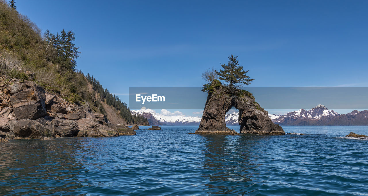water, sky, waterfront, beauty in nature, scenics - nature, sea, tranquil scene, rock, tranquility, blue, nature, rock - object, day, no people, solid, idyllic, tree, non-urban scene, rock formation, outdoors