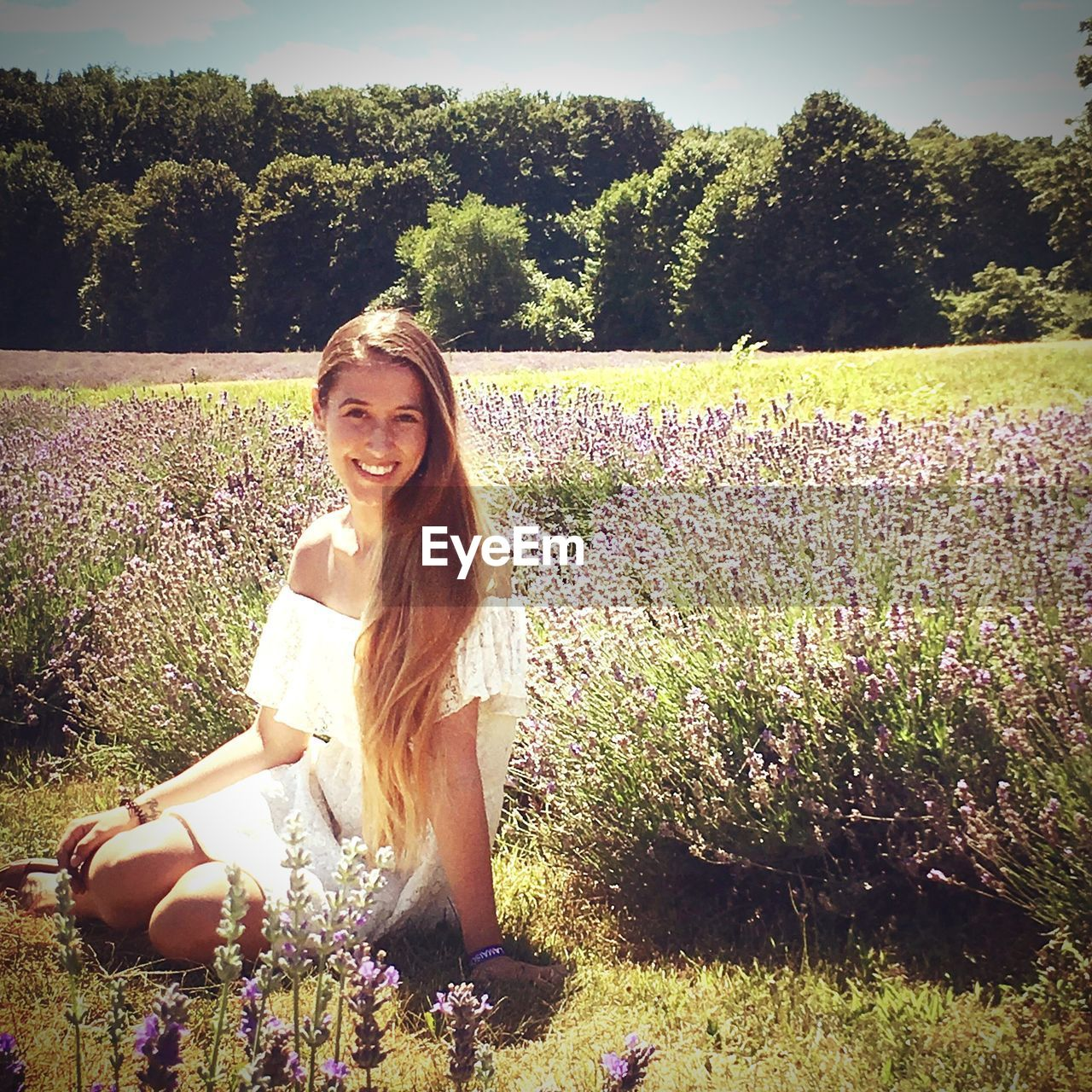 plant, looking at camera, portrait, real people, one person, smiling, leisure activity, flowering plant, flower, young women, tree, women, lifestyles, nature, young adult, growth, field, land, sunlight, hairstyle, hair, beautiful woman, outdoors