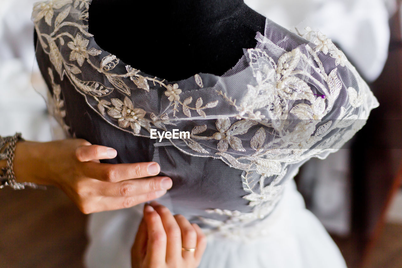 Cropped Image Of Fashion Designer Adjusting Wedding Dress On Mannequin