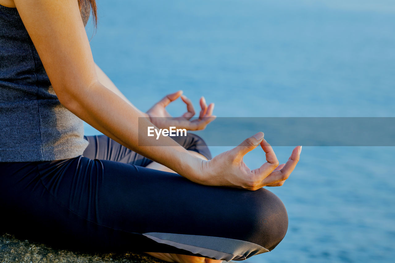 Midsection Of Woman Practicing Yoga At Beach