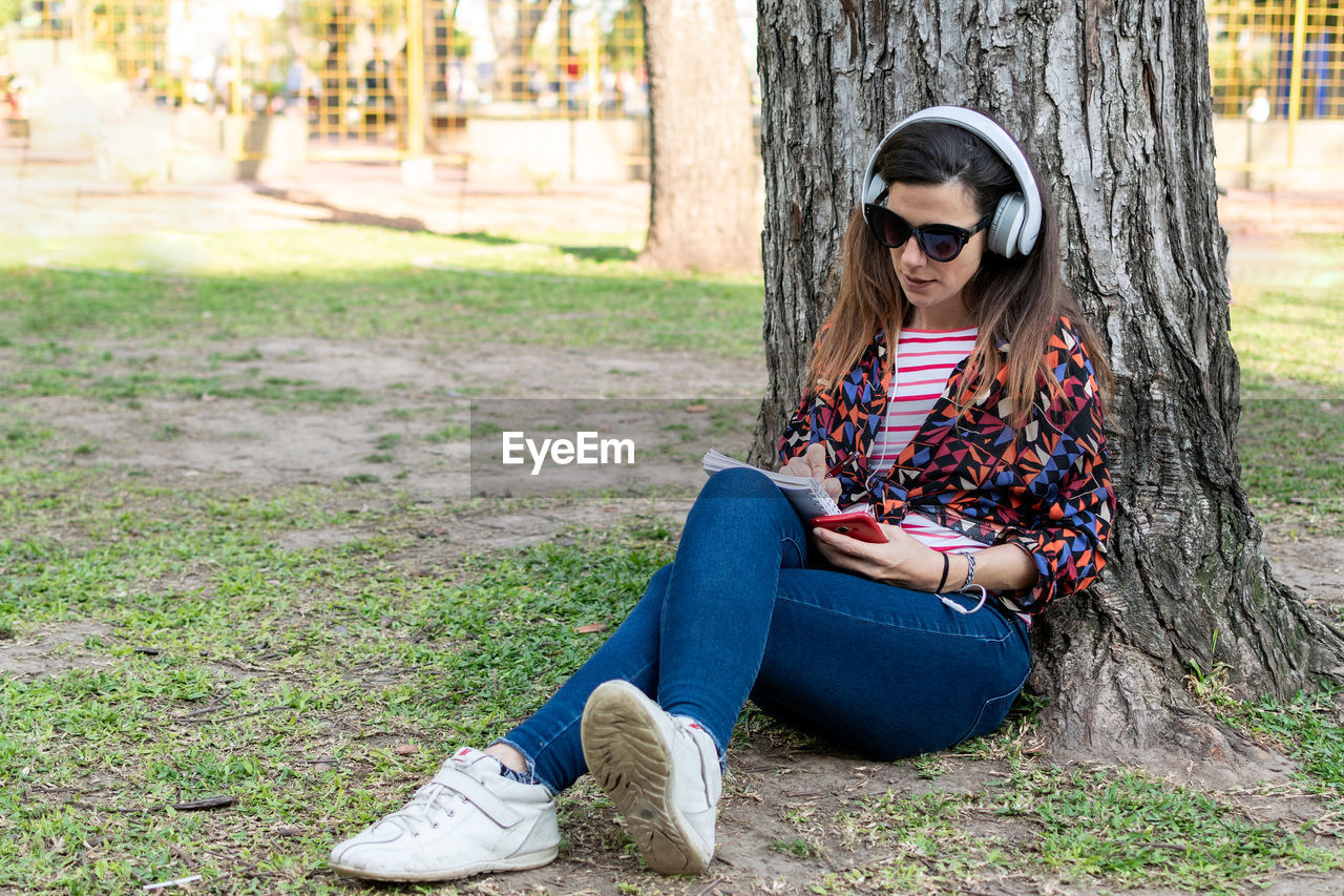 YOUNG WOMAN WEARING SUNGLASSES SITTING ON TREE TRUNK