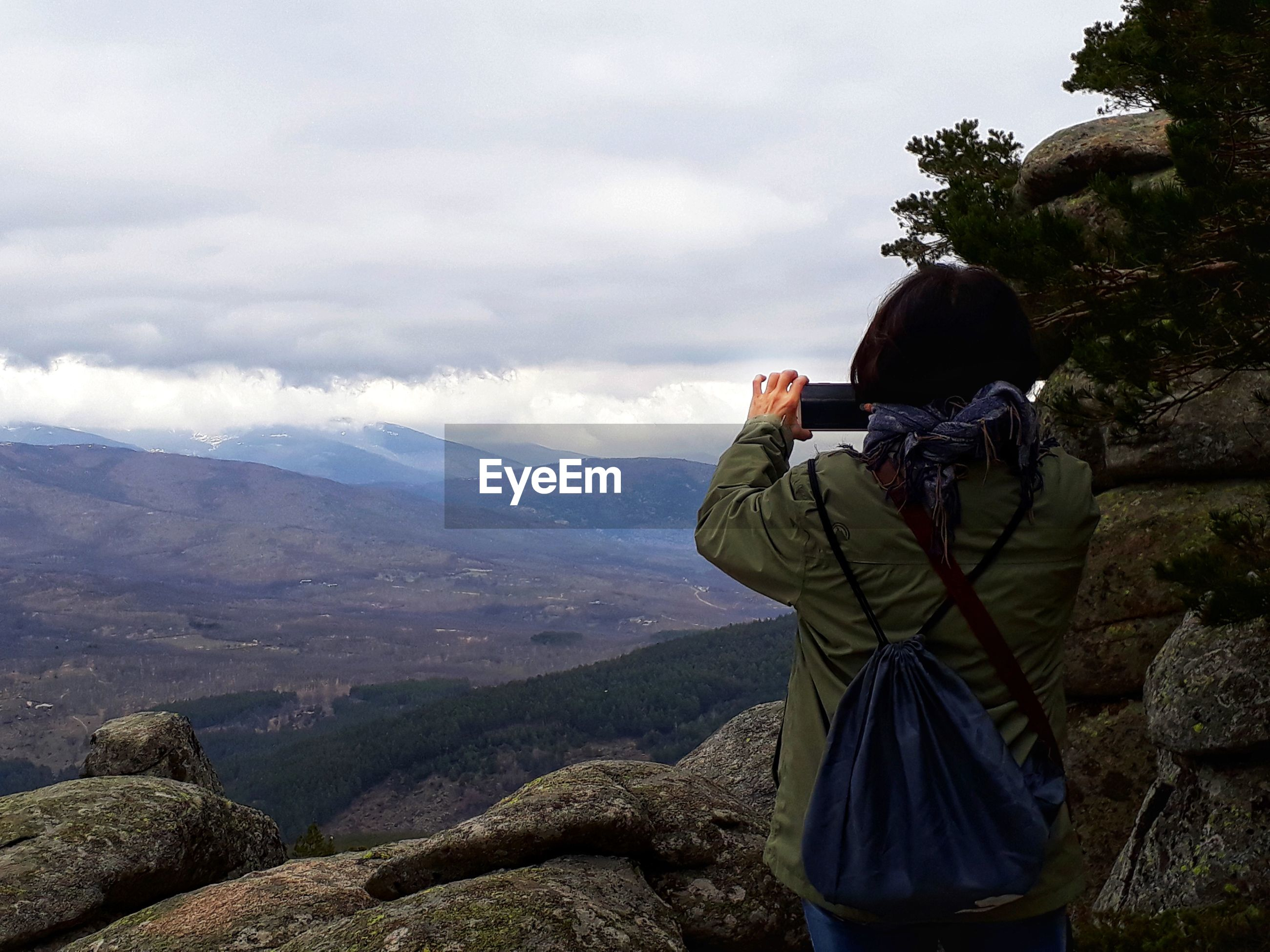 Rear view of woman photographing mountains against sky