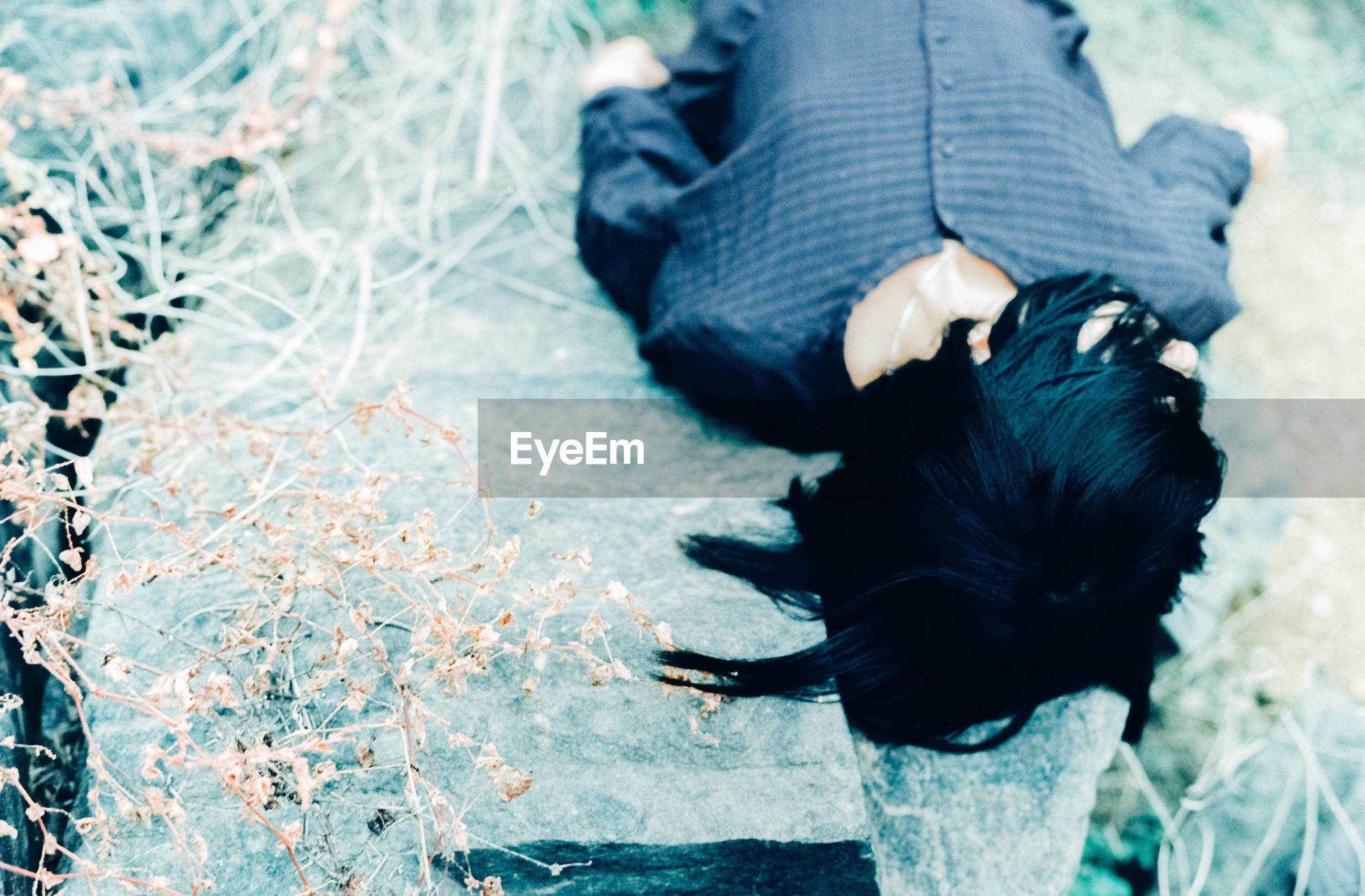 High angle view of woman lying on rocks