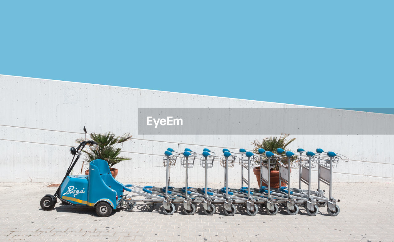 land vehicle, transportation, stationary, mode of transport, blue, day, bicycle, built structure, outdoors, architecture, sunlight, clear sky, no people, scooter, building exterior, shopping cart, bicycle rack, sky