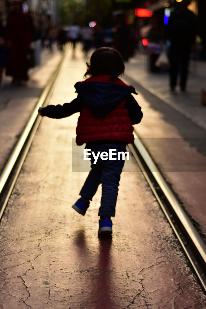 real people, childhood, child, one person, transportation, full length, lifestyles, rear view, walking, women, track, rail transportation, railroad track, leisure activity, mode of transportation, girls, casual clothing, city, females, outdoors, warm clothing