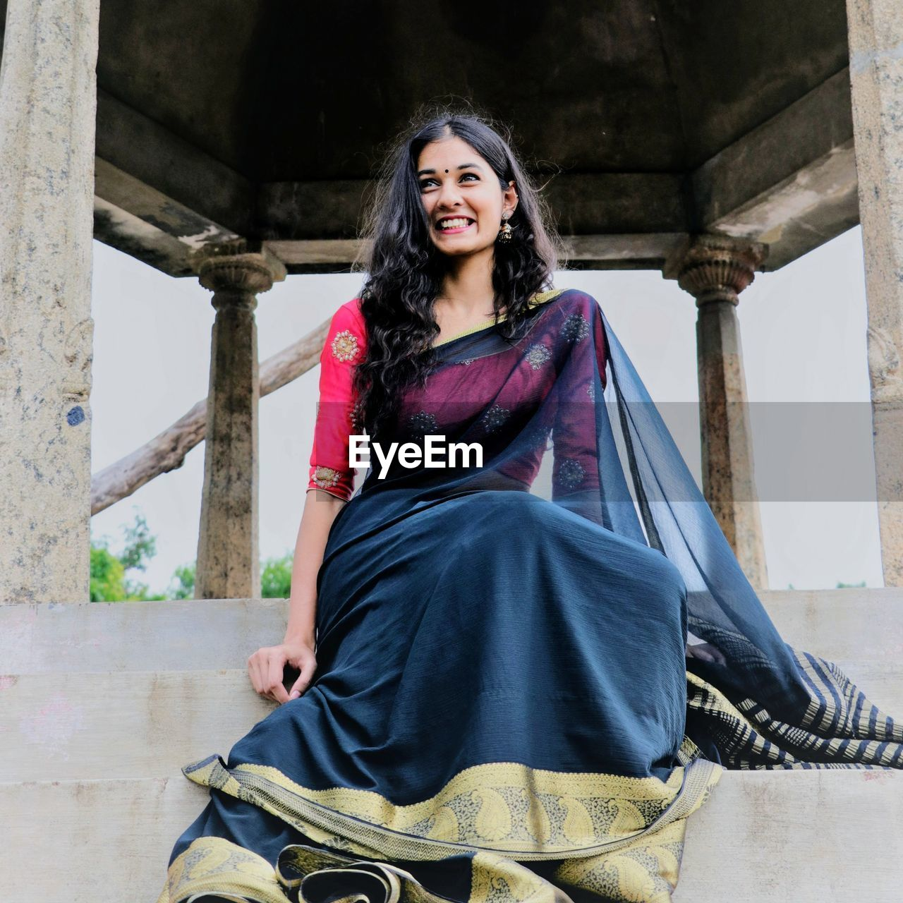Low Angle View Of Cheerful Woman Wearing Sari While Sitting On Steps