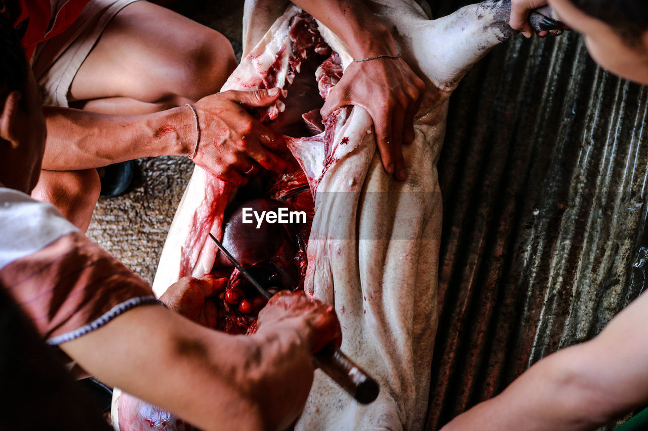 High Angle View Of Butchers Cutting Meat