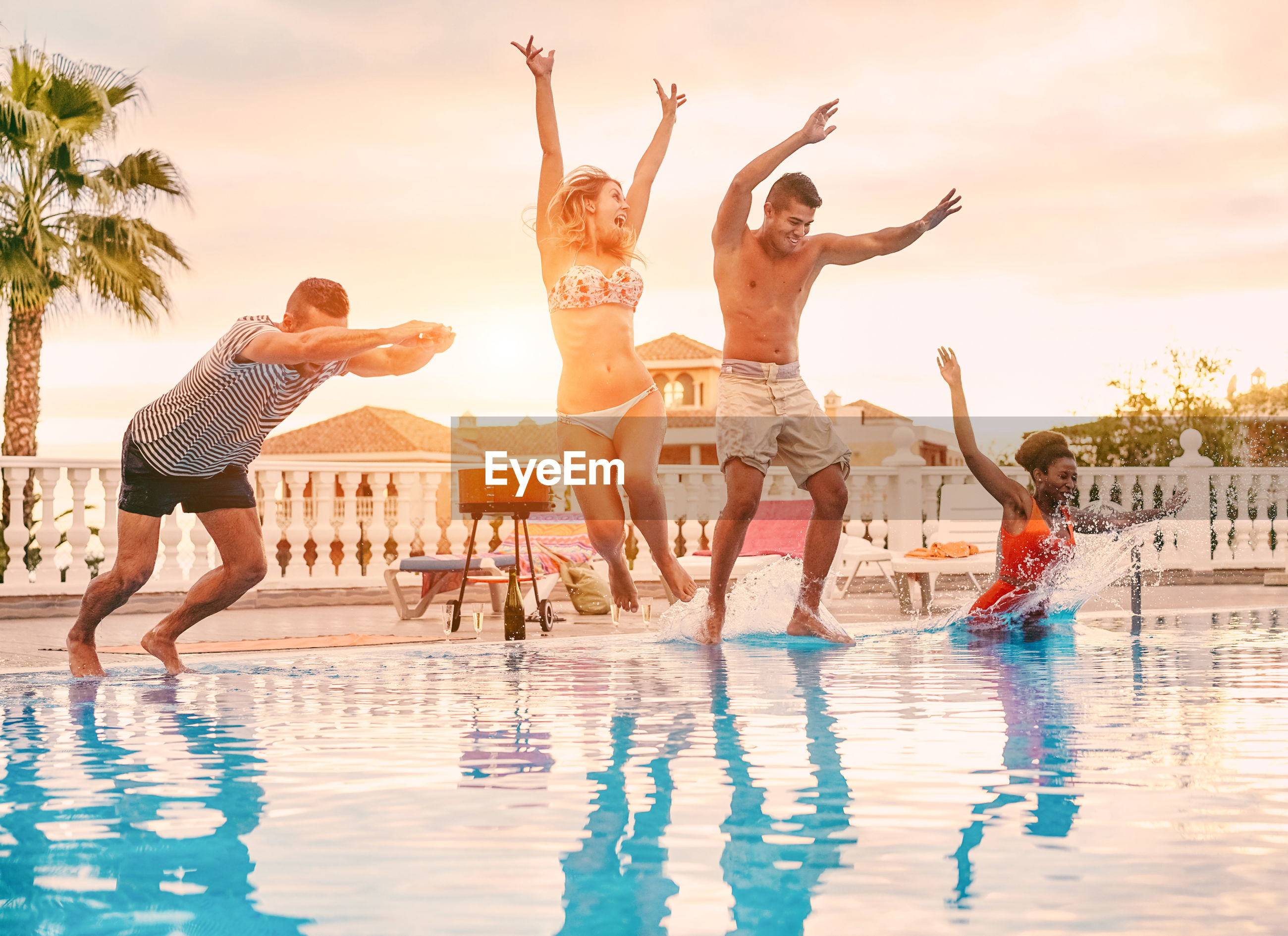Friends jumping in swimming pool against sky during sunset