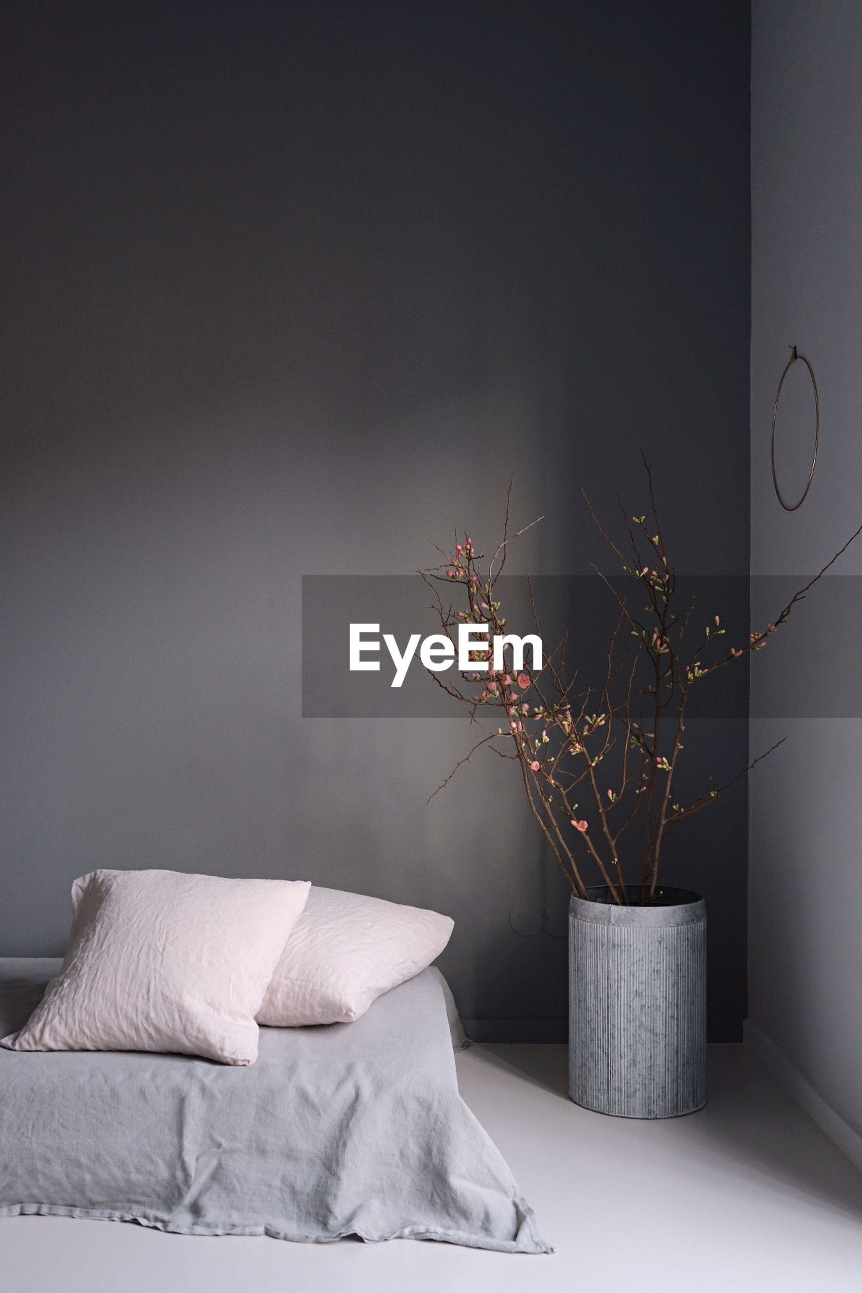 Vase by bed against gray wall at home