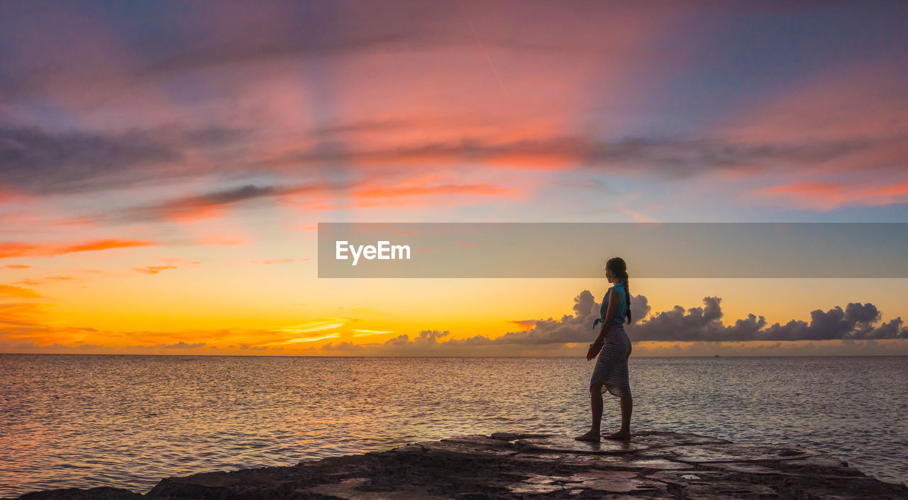 sunset, sky, beauty in nature, sea, orange color, water, cloud - sky, one person, standing, scenics - nature, real people, land, leisure activity, beach, lifestyles, tranquility, idyllic, tranquil scene, nature, outdoors, horizon over water
