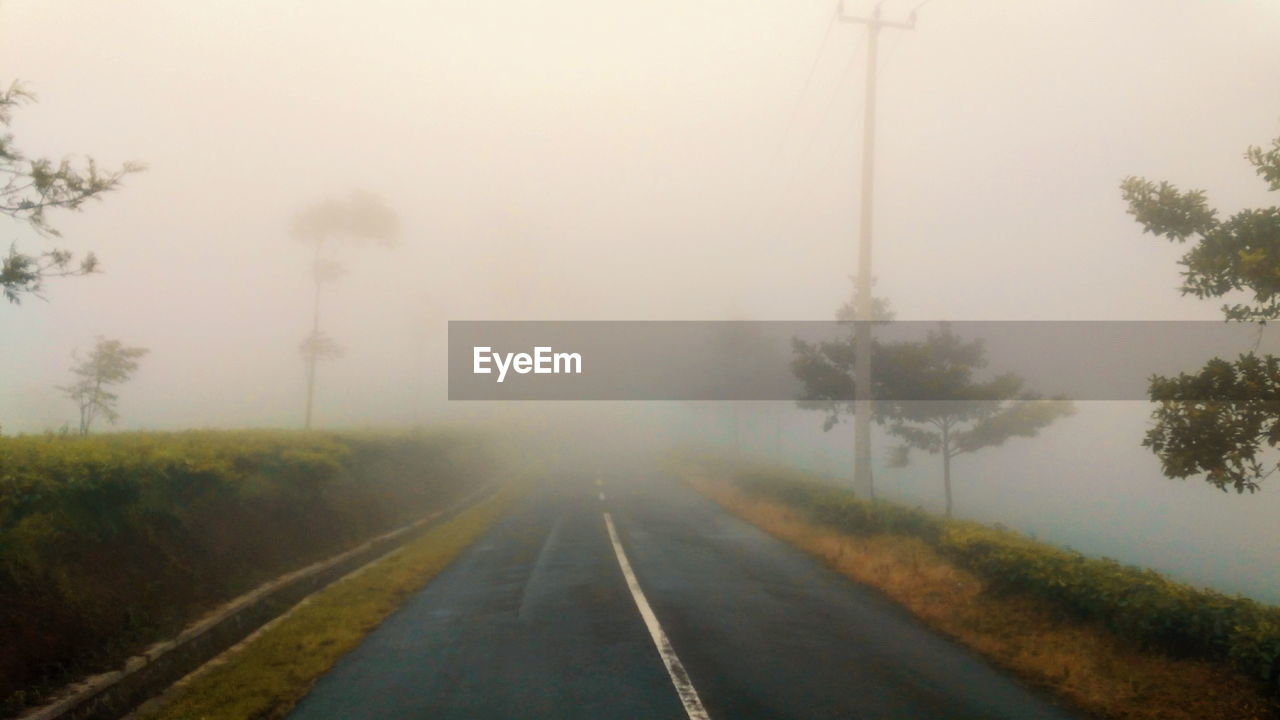 ROAD IN FOGGY WEATHER AGAINST SKY
