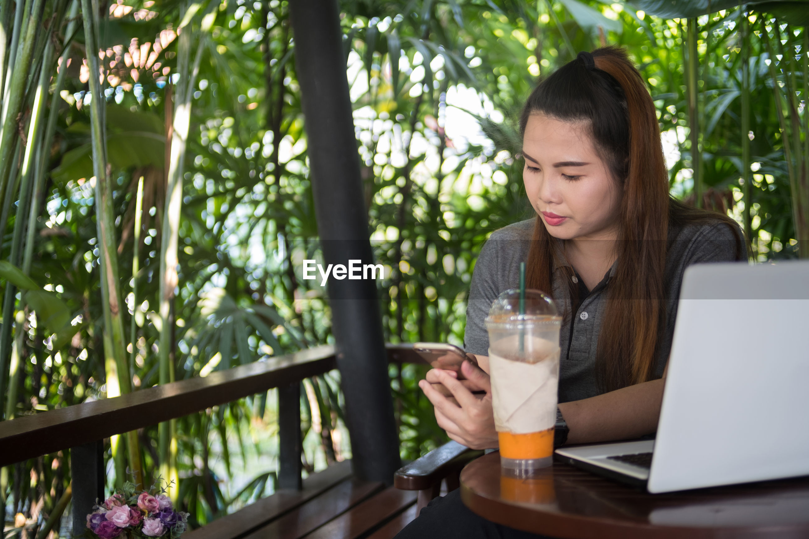 Young woman using mobile phone at table in restaurant