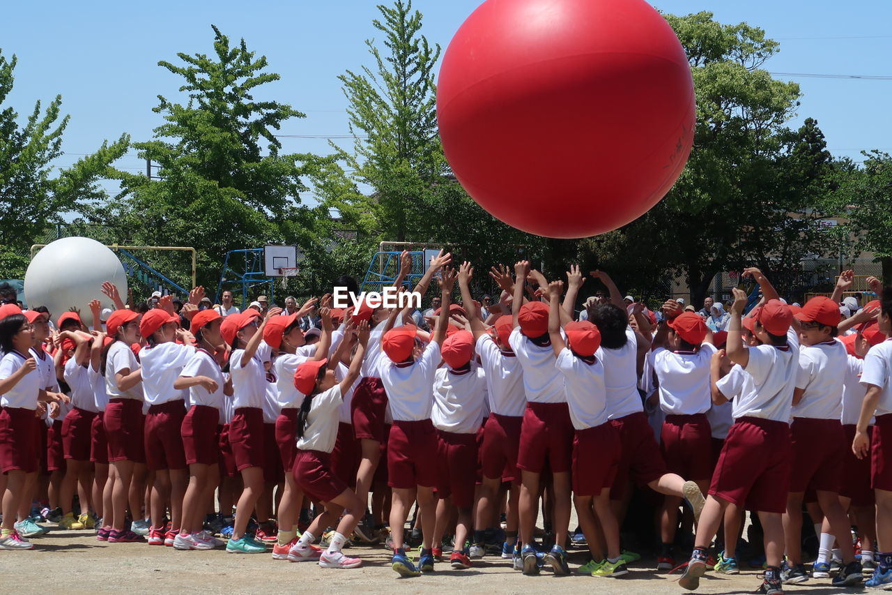 Students Playing With Red Large Ball In City