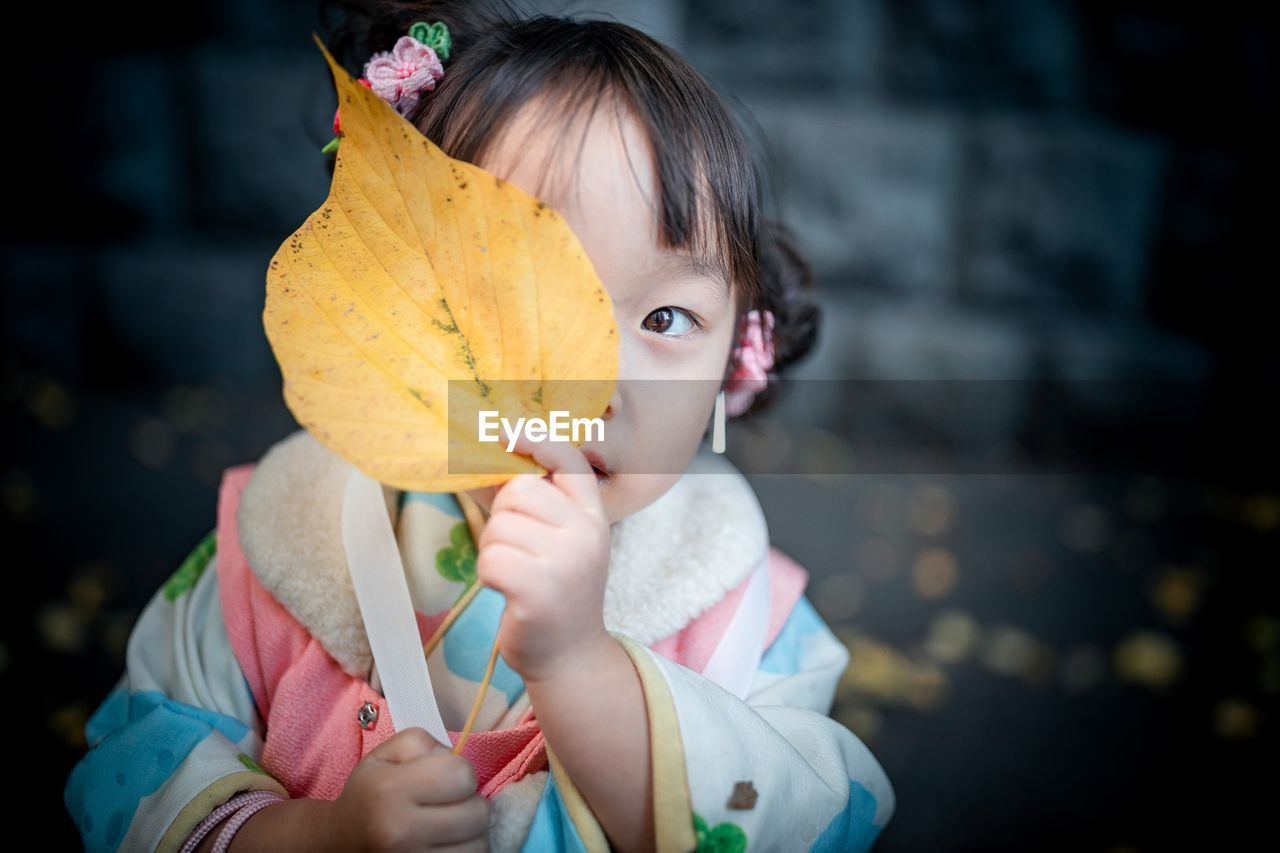 Portrait Of Cute Girl Covering Face With Leaf