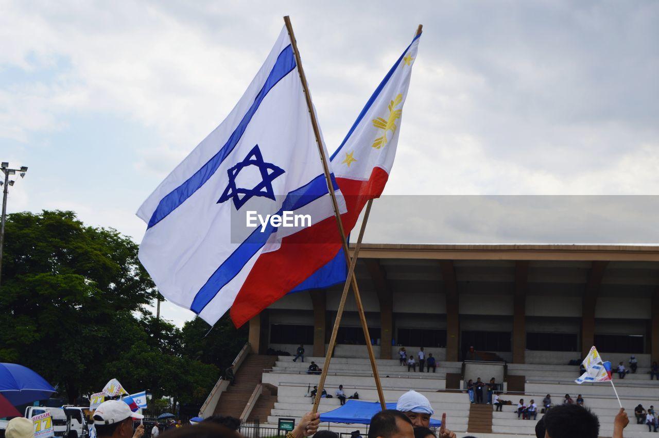 GROUP OF PEOPLE FLAG AGAINST BUILDINGS