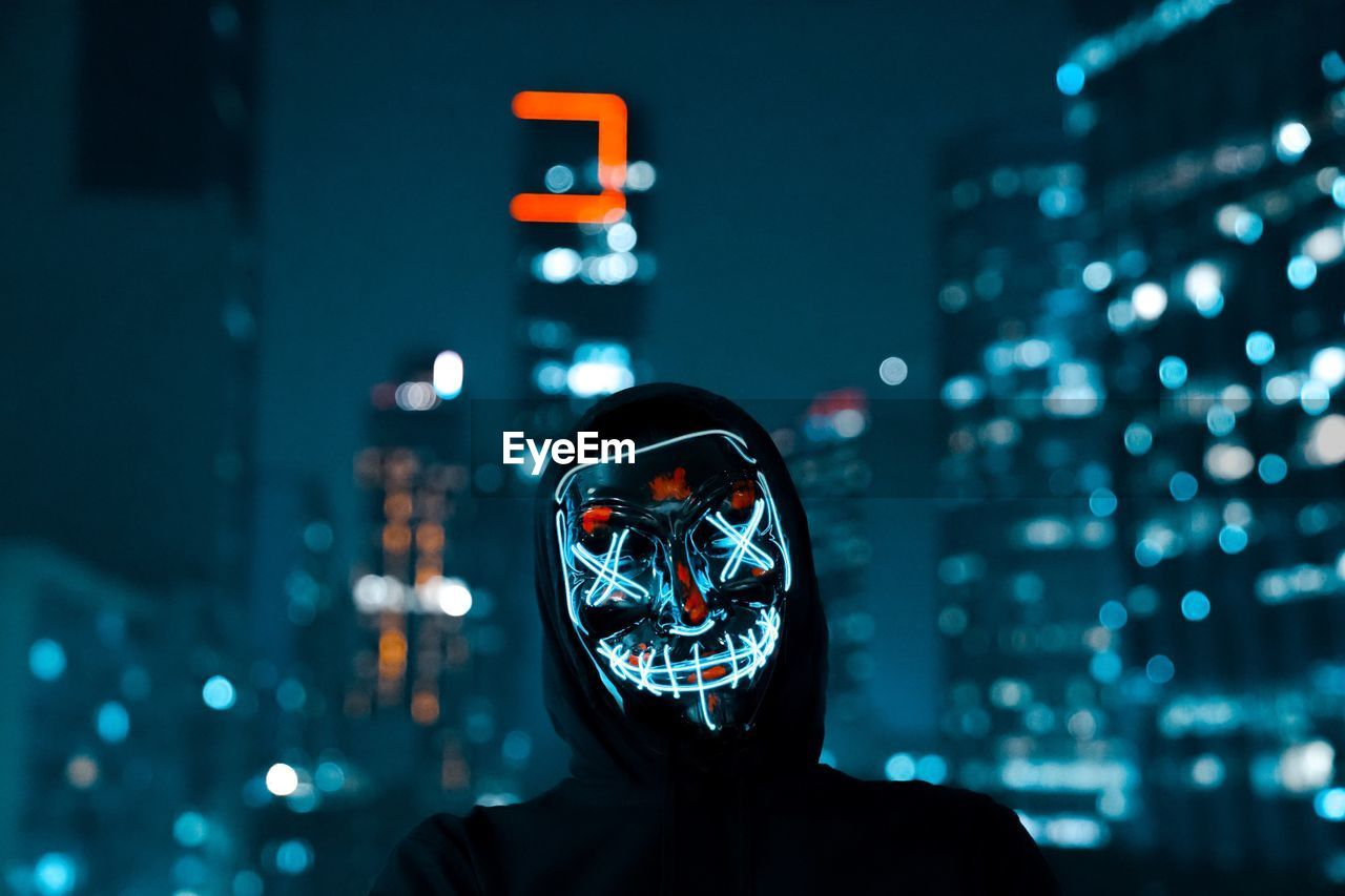 Man Wearing Illuminated Mask In City At Night