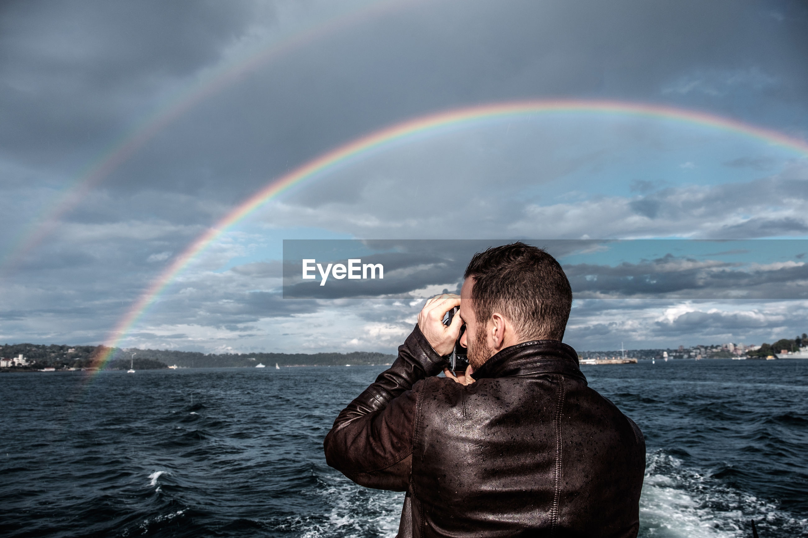 Scenic view of man taking photograph of  rainbow in front of sea against sky