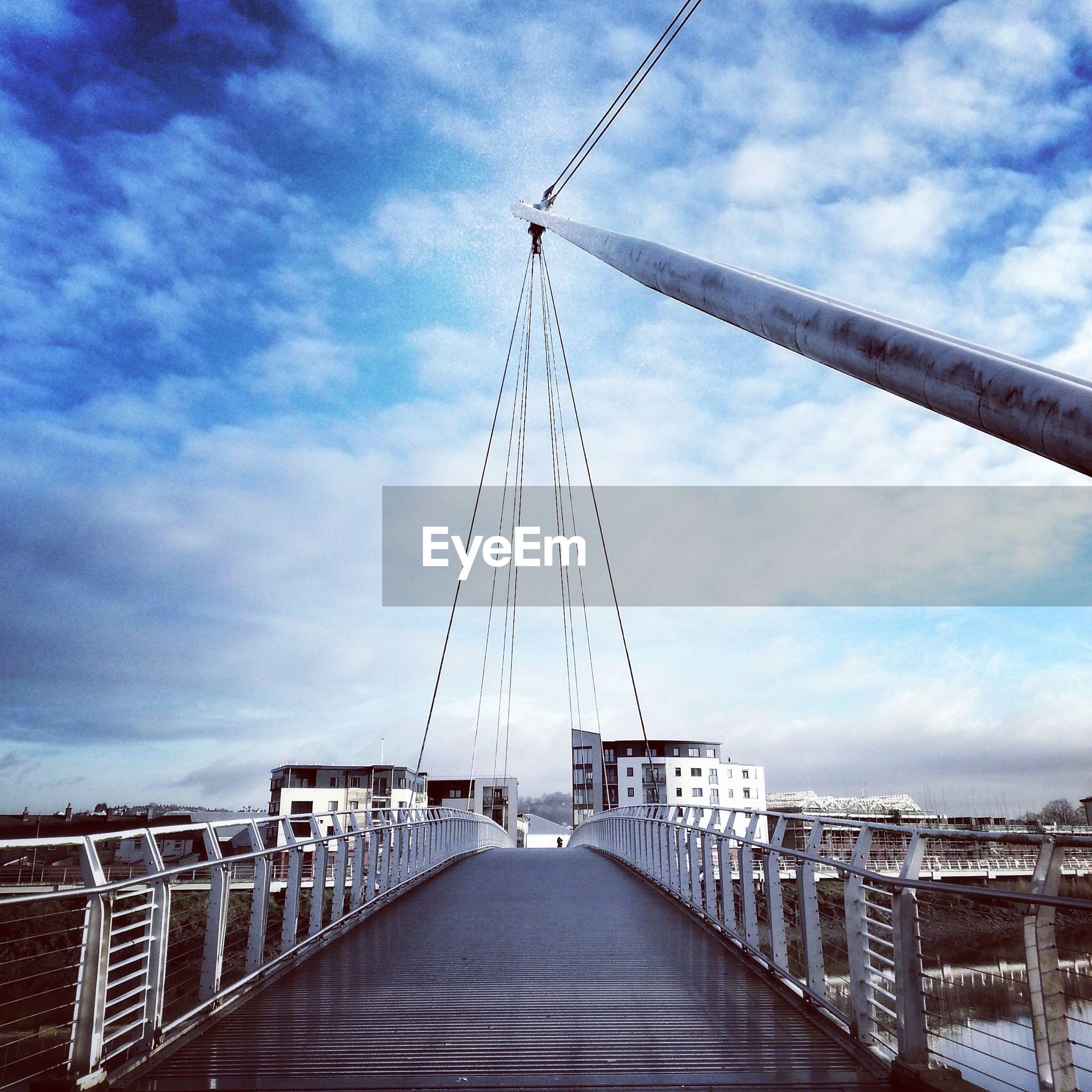 Footbridge over canal against cloudy sky