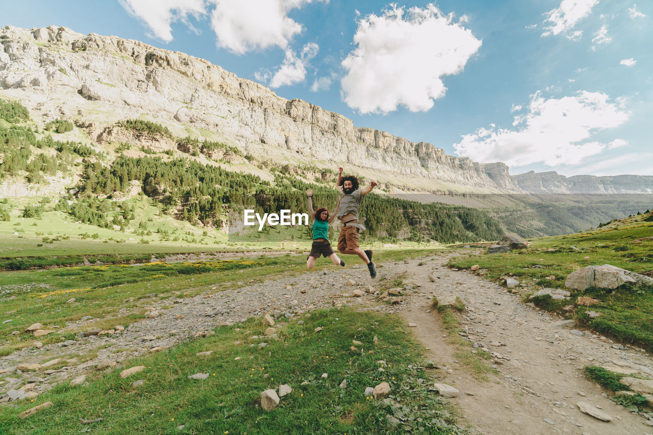 Couple jumping against mountains on field