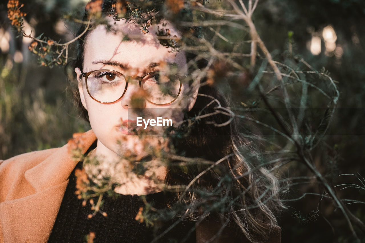 portrait, headshot, one person, looking at camera, plant, young adult, leisure activity, real people, focus on foreground, front view, lifestyles, nature, close-up, day, glasses, eyeglasses, leaf, plant part, outdoors, hairstyle, teenager, human face, beautiful woman