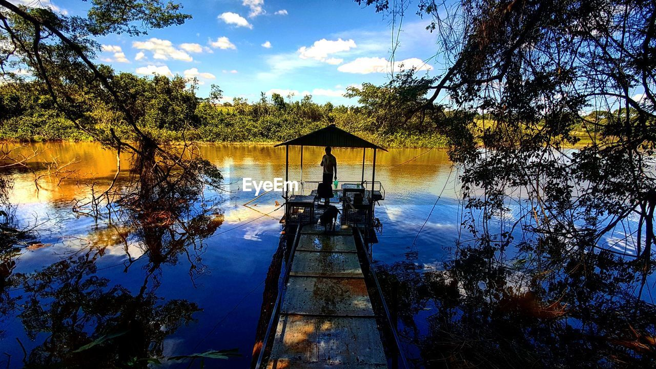 tree, sky, water, nature, real people, beauty in nature, lake, cloud - sky, outdoors, transportation, scenics, tranquility, growth, tranquil scene, silhouette, leisure activity, day, nautical vessel, men, forest, one person, branch, people