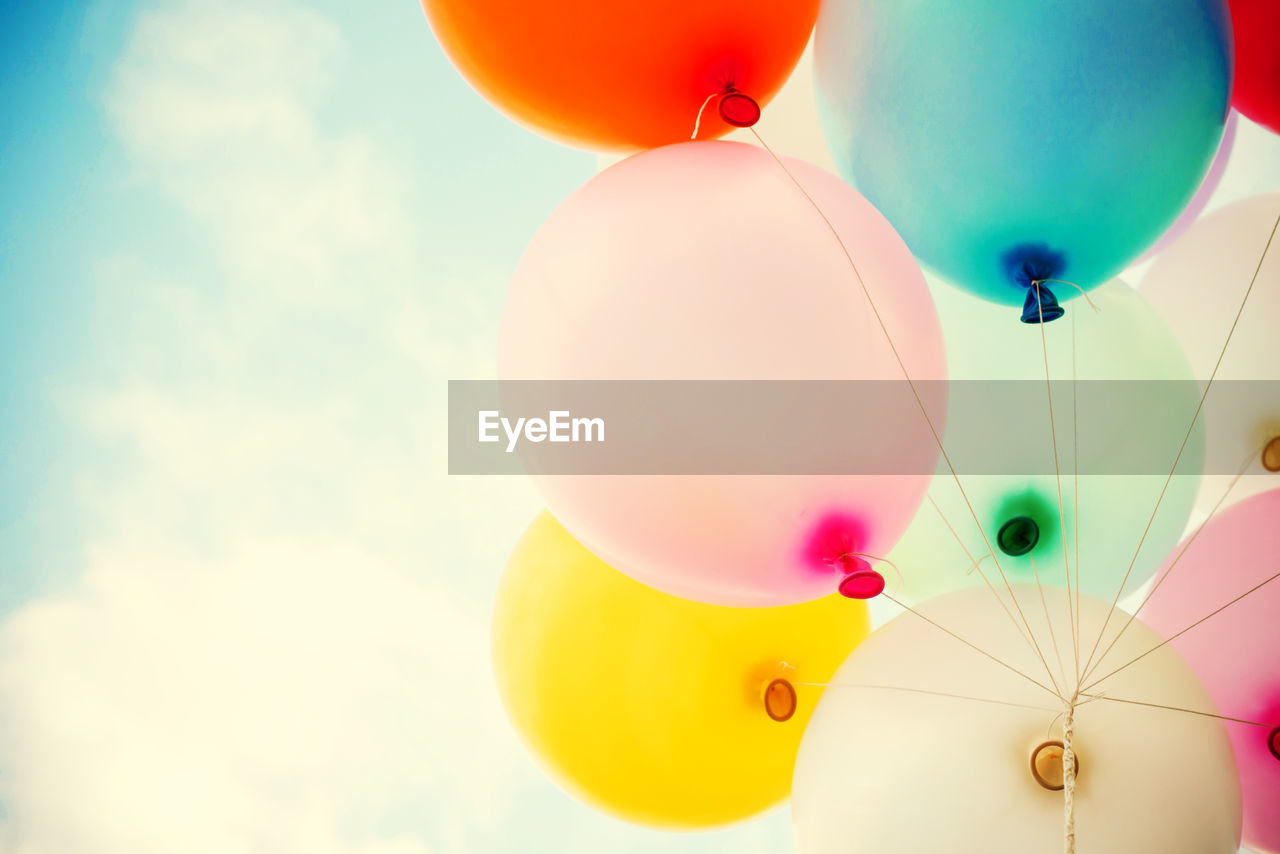 balloon, multi colored, sky, low angle view, celebration, no people, cloud - sky, nature, mid-air, helium balloon, day, decoration, vulnerability, close-up, flying, group of objects, fragility, outdoors, variation, ceiling