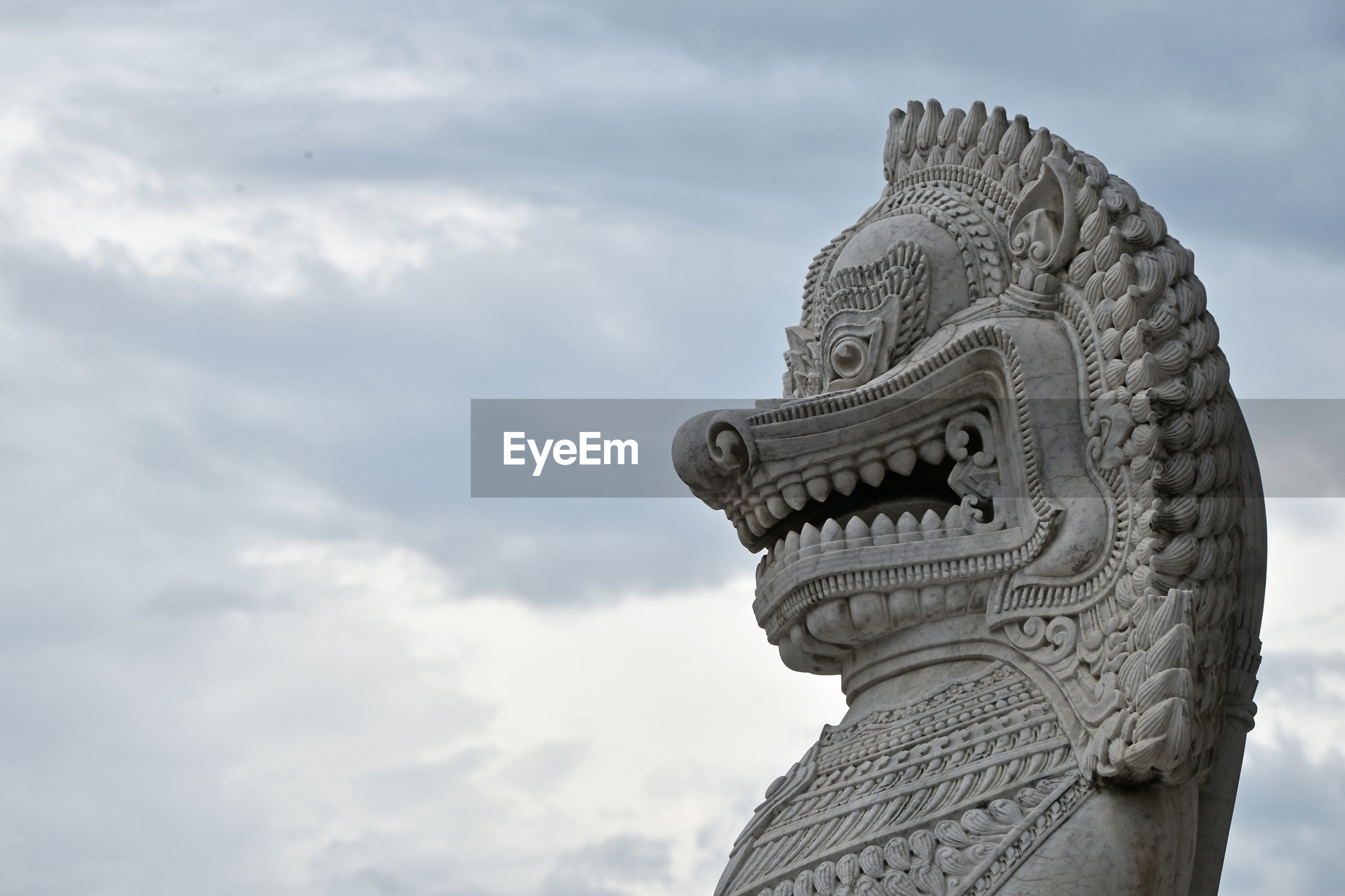 Statue against cloudy sky