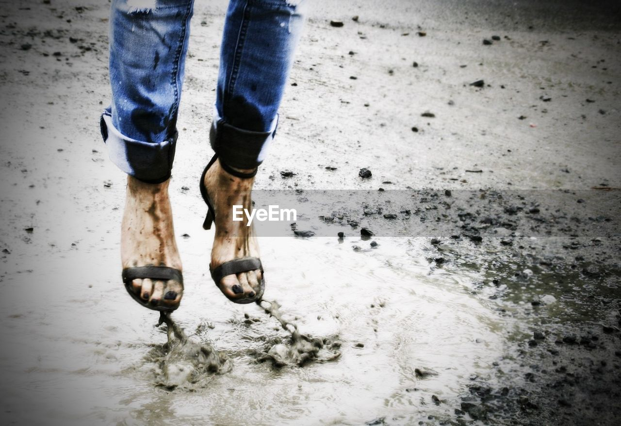 Low Section Of Woman Jumping Over Mud During Monsoon
