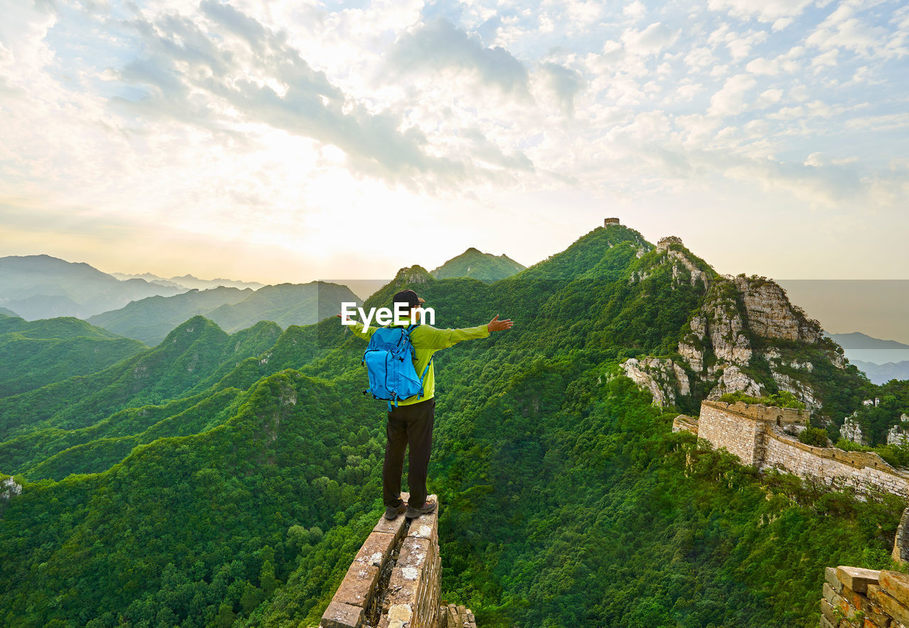 Rear view of man with arms outstretched standing on cliff at great wall of china