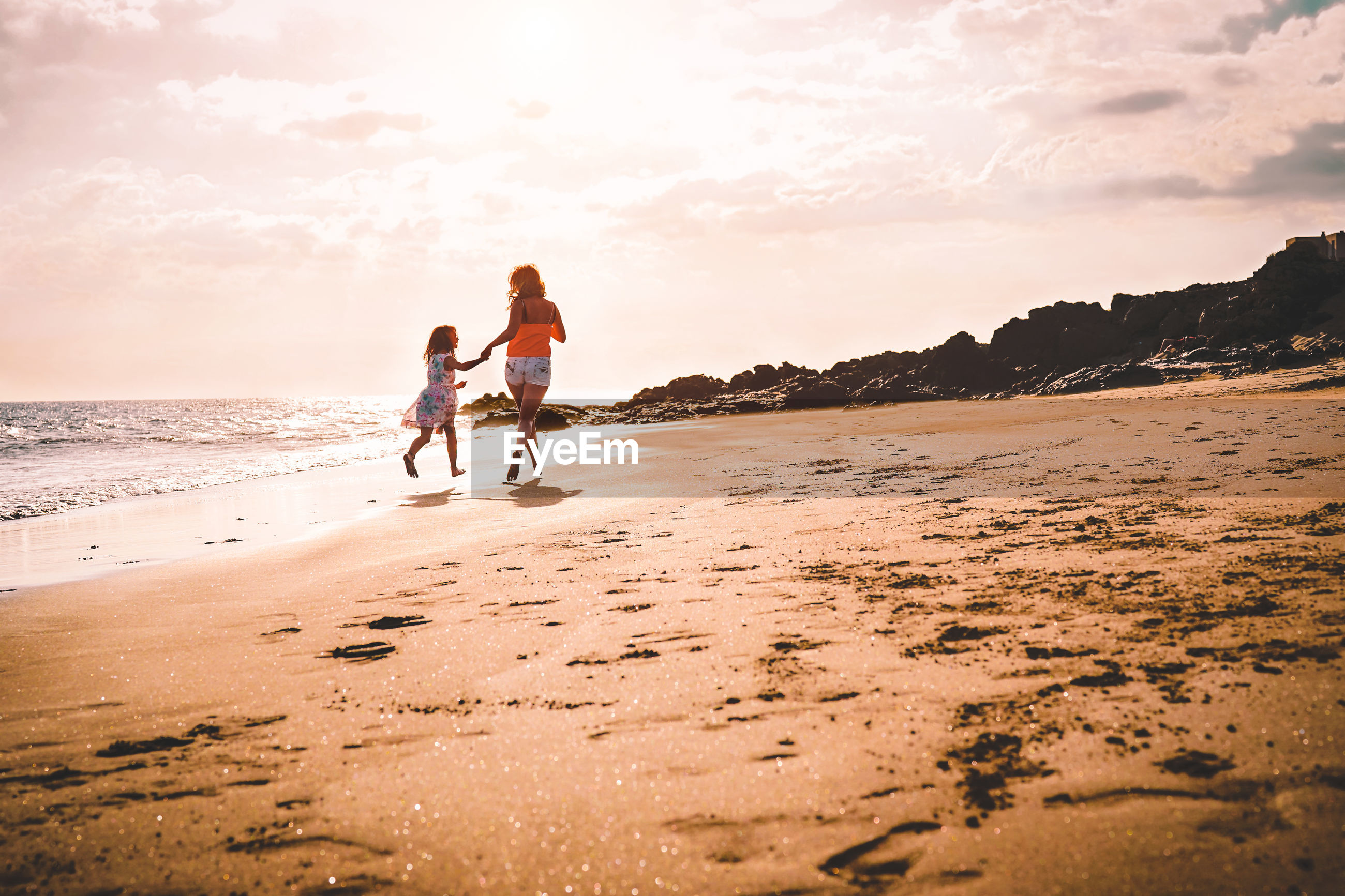 Full length of mother and daughter playing on shore at beach against sky during sunset