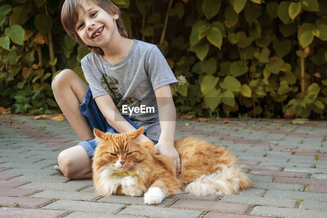 Happy and joyful boy smiles and strokes his pet - red cat.