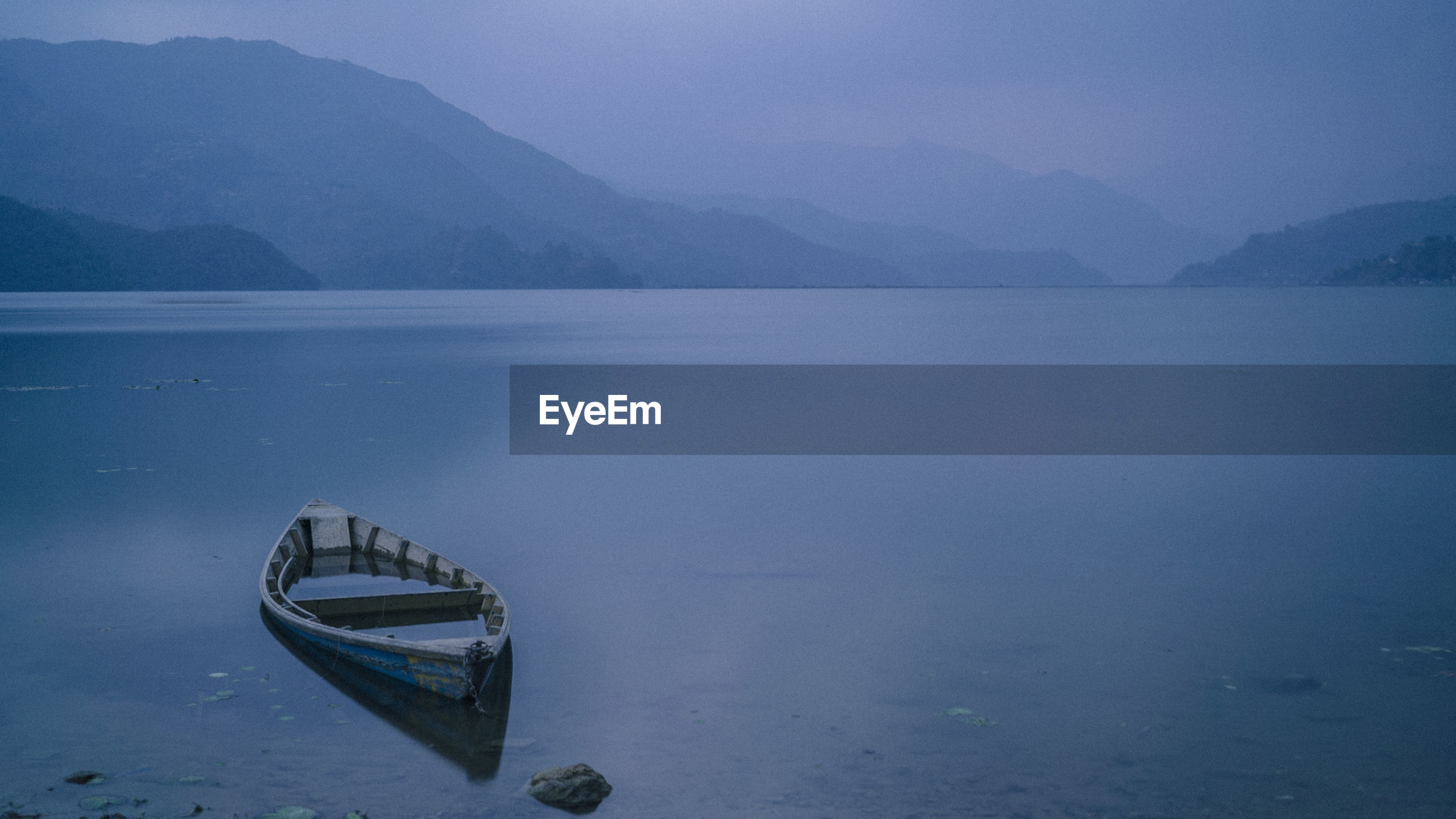 Boat moored on lake against sky during sunrise