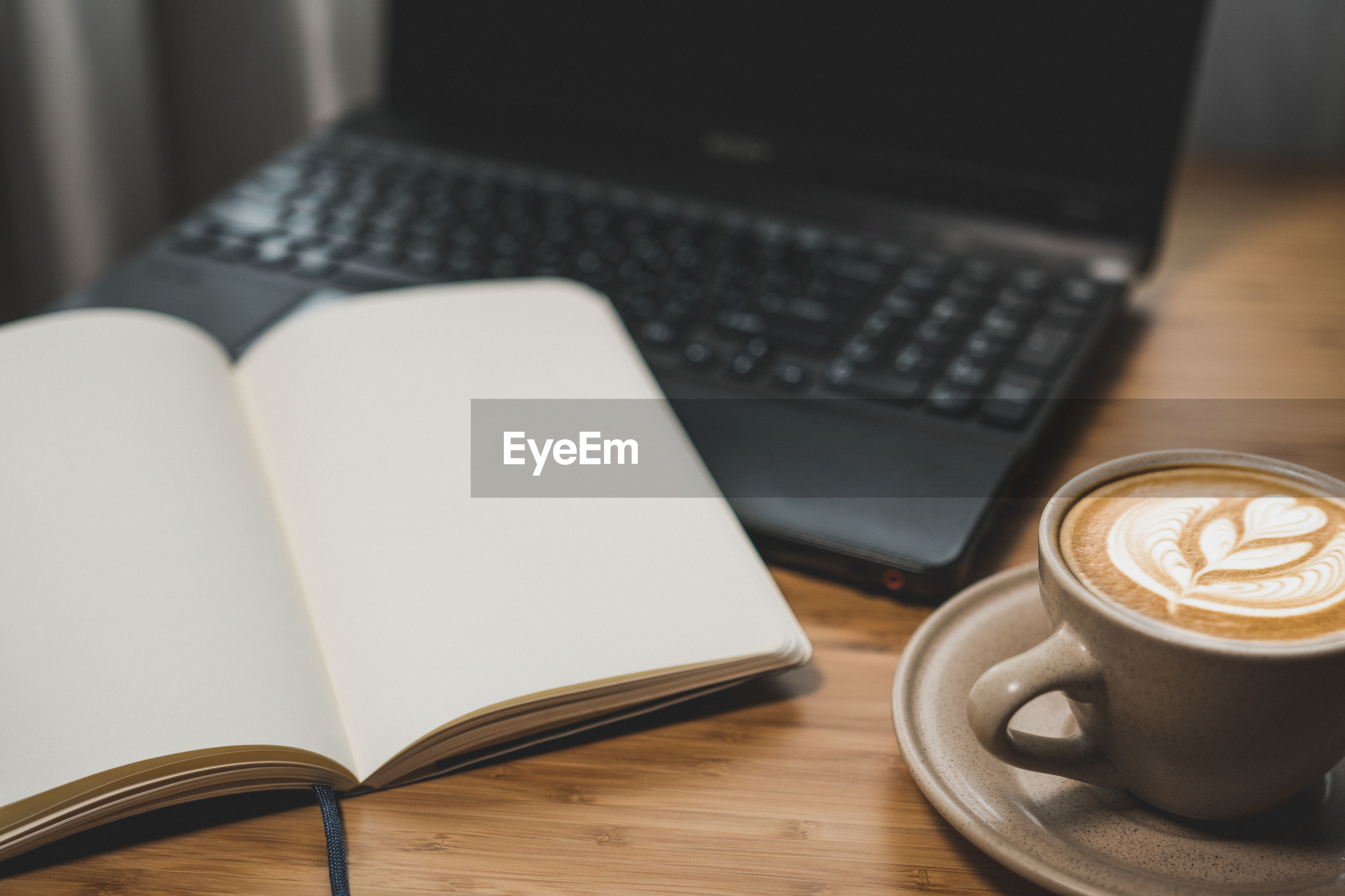 Coffee cup and book with laptop on table