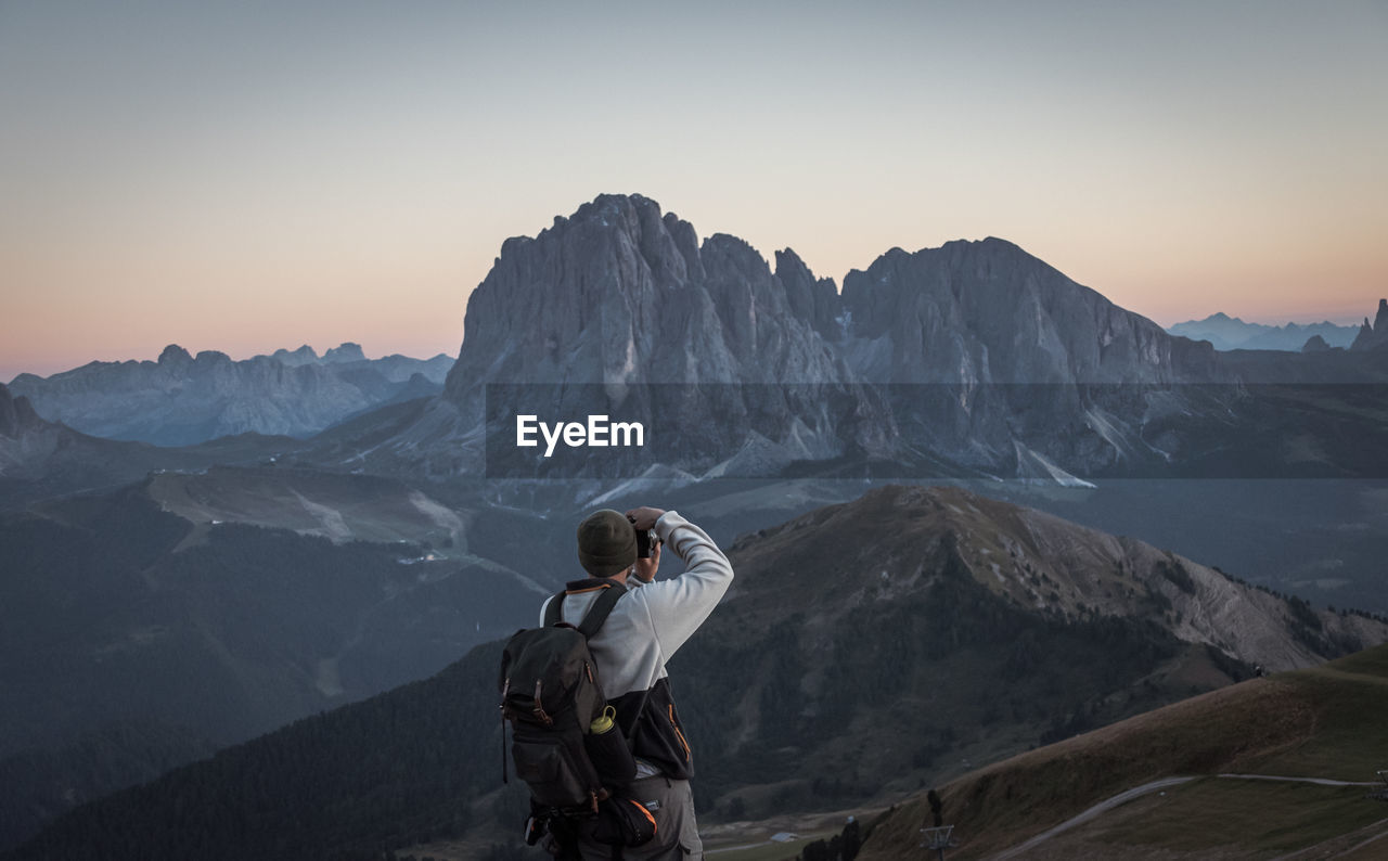 Man photographing on snowcapped mountains against sky