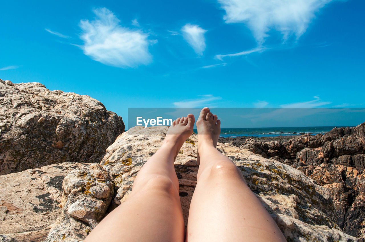 Low Section Of Young Woman Lying On Rock By Sea Against Blue Sky During Sunny Day
