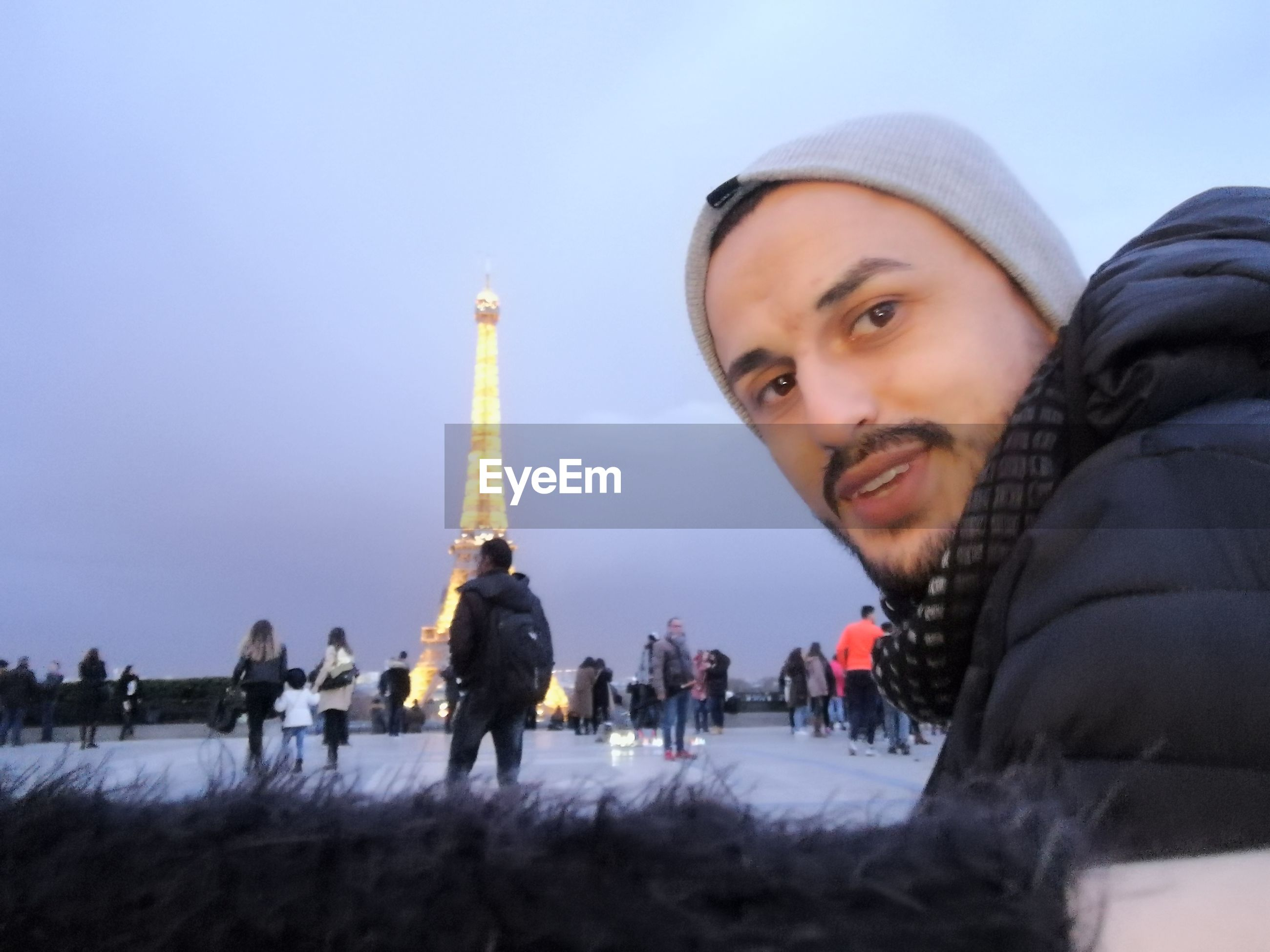 Portrait of man against illuminated eiffel tower at dusk