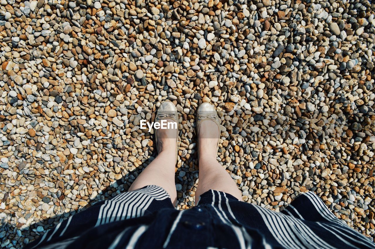 Low Section Of Woman Standing On Pebbles