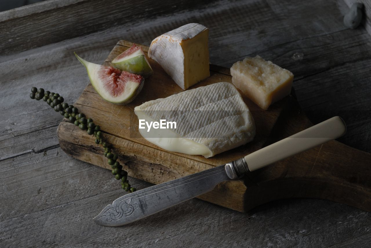 High Angle View Of Cheese On Cutting Board Over Table