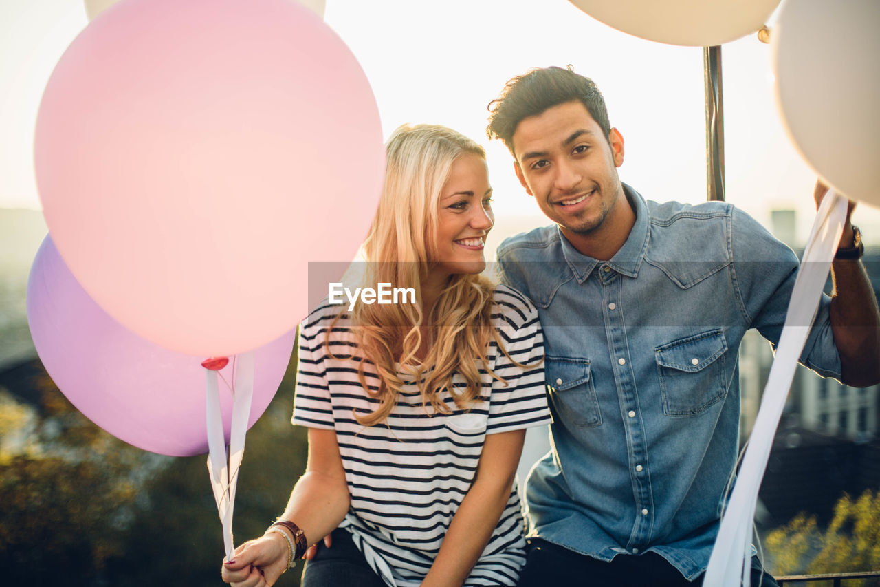 Couple Sitting With Balloons Against Sky