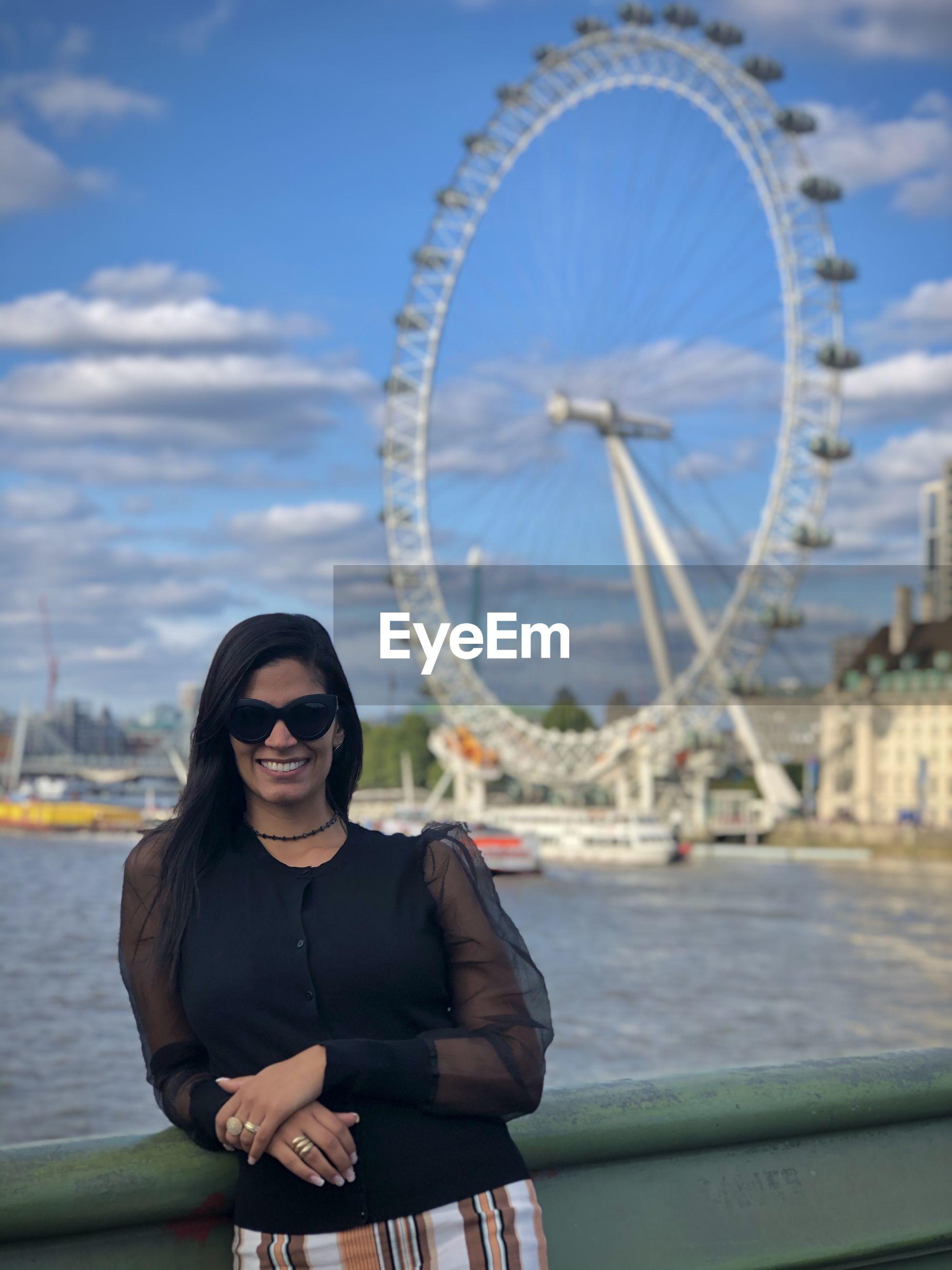 Portrait of woman wearing sunglasses against ferris wheel by river in city