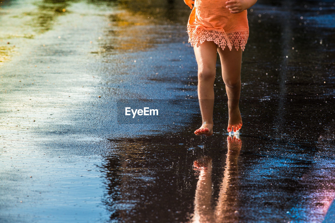 Low Section Of Girl On Wet Street During Rainy Season