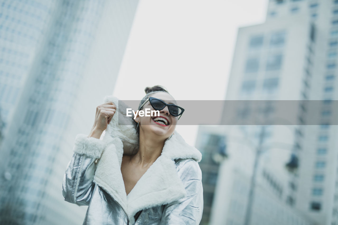 building exterior, architecture, young adult, city, lifestyles, one person, leisure activity, glasses, built structure, happiness, women, young women, smiling, focus on foreground, real people, adult, office building exterior, day, fashion, skyscraper, beautiful woman, warm clothing