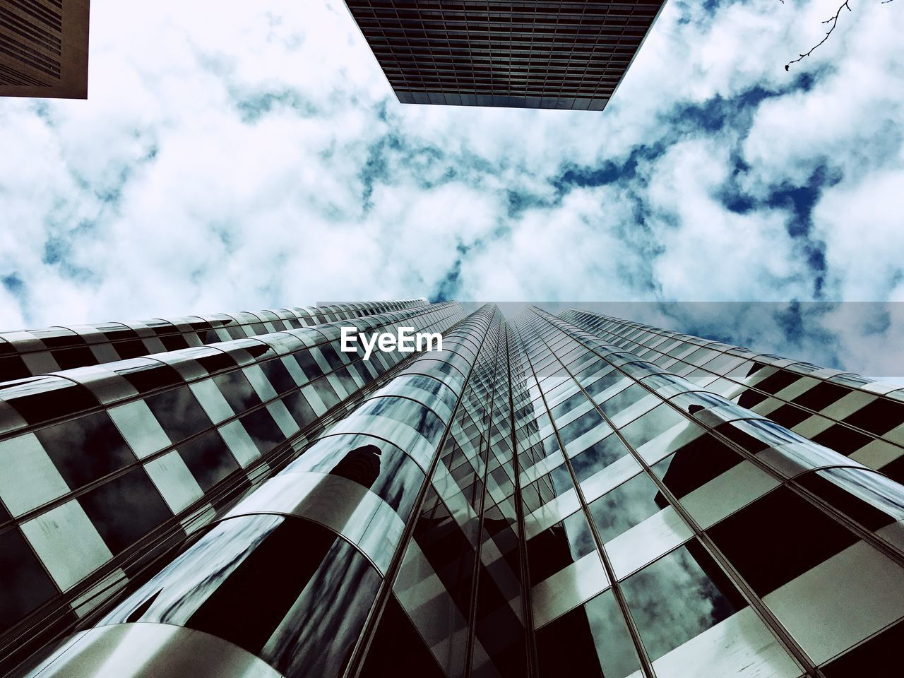 Directly Below Shot Of Modern Building Against Cloudy Sky