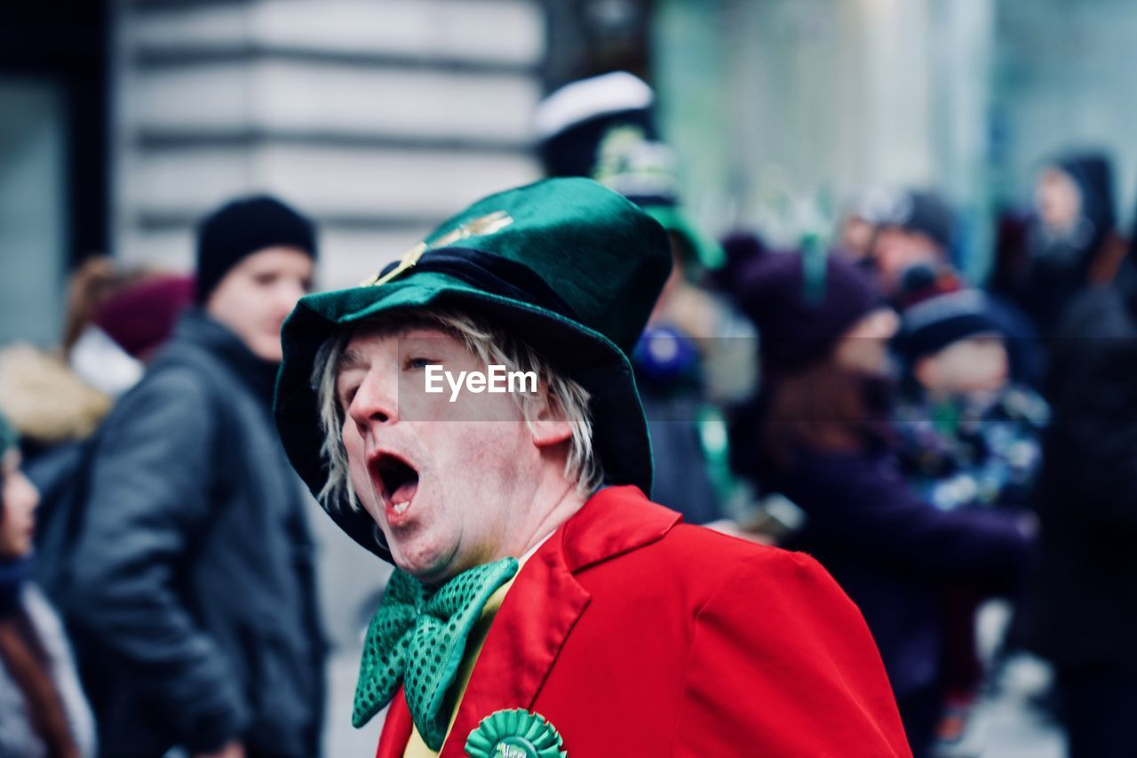 mouth open, focus on foreground, real people, human mouth, screaming, incidental people, shouting, day, headshot, human body part, men, close-up, outdoors, young adult, warm clothing, one person, people